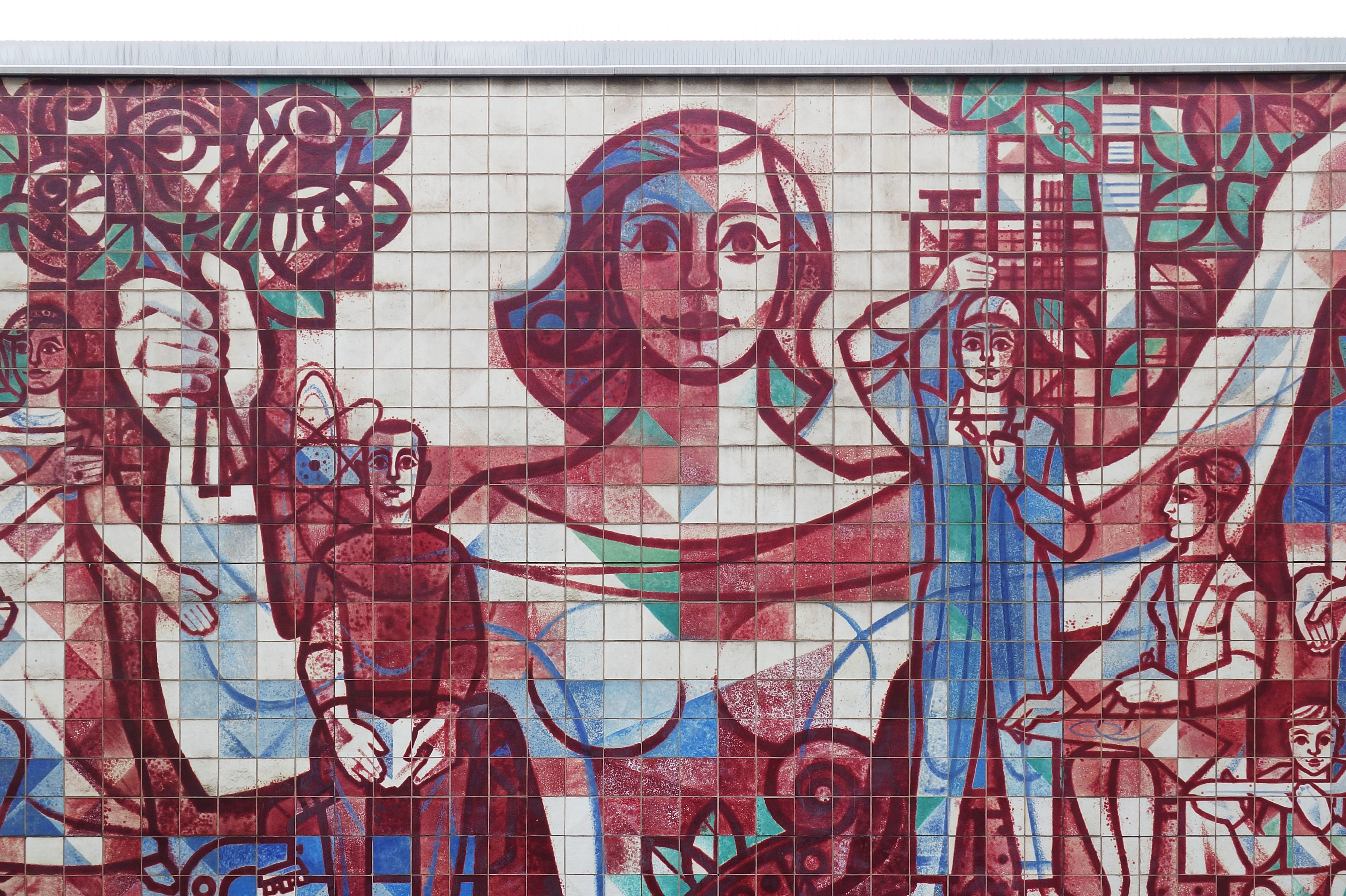 Red graffiti artwork mural of people on mosaic wall in Seevorstadt West, Dresden, Saxony, Germany