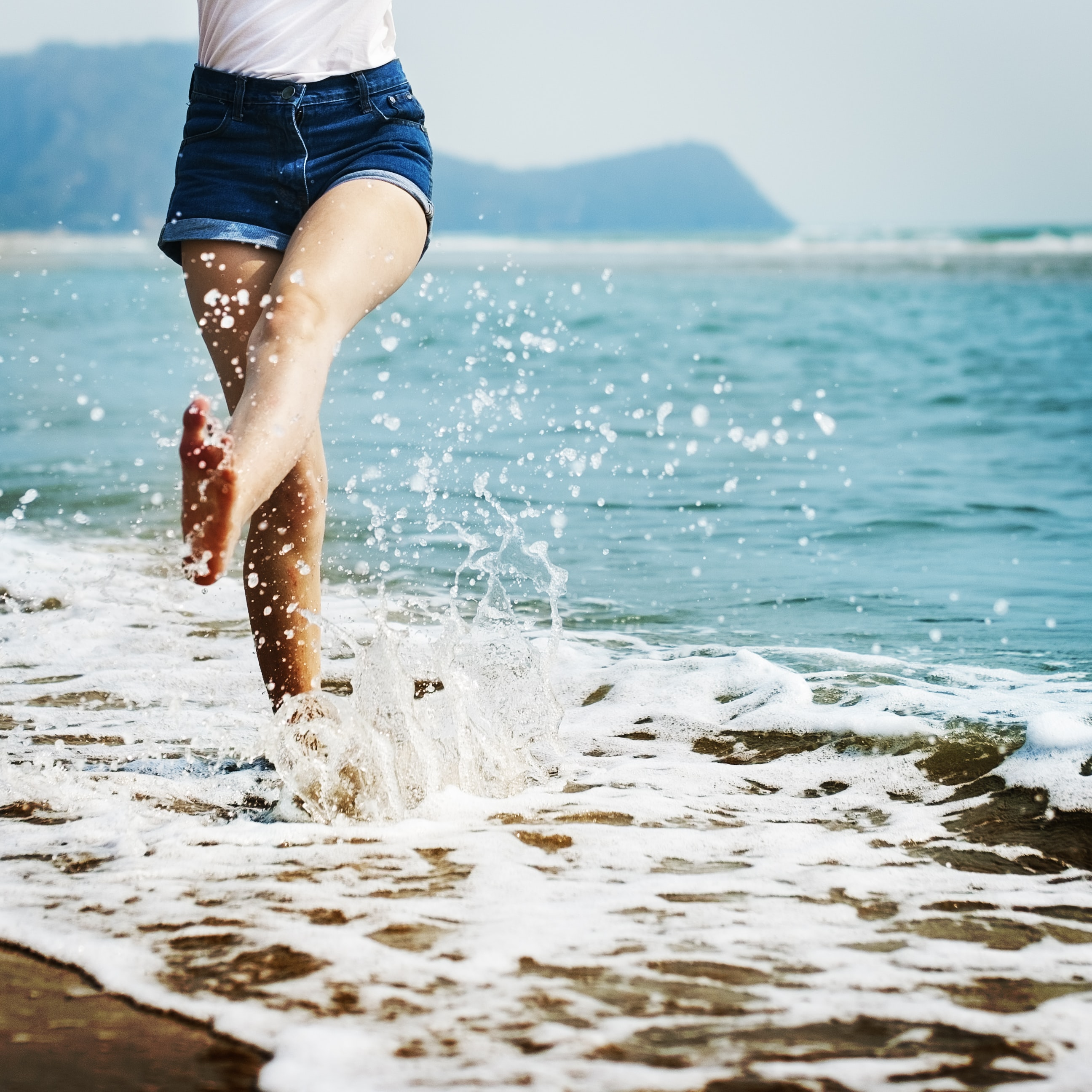 A girl wearing jean shorts splashing her feet in the ocean