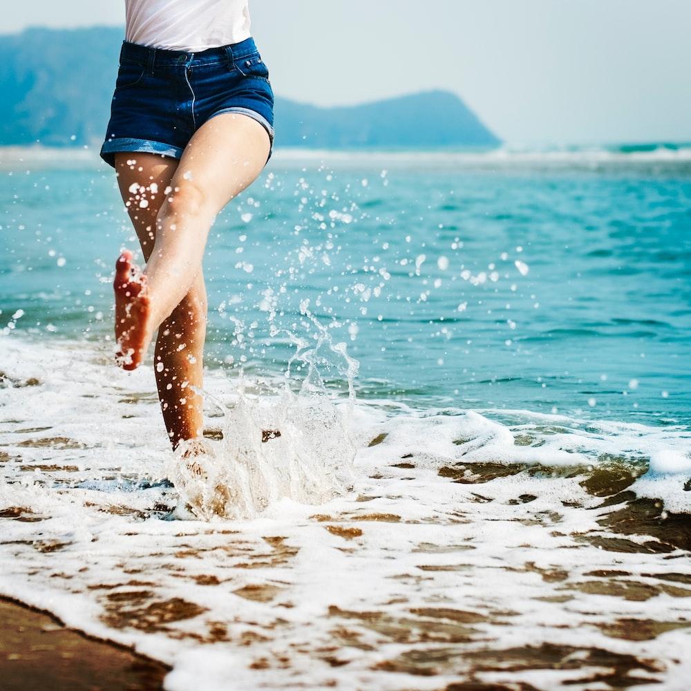 woman wearing blue denim shorts on seashore