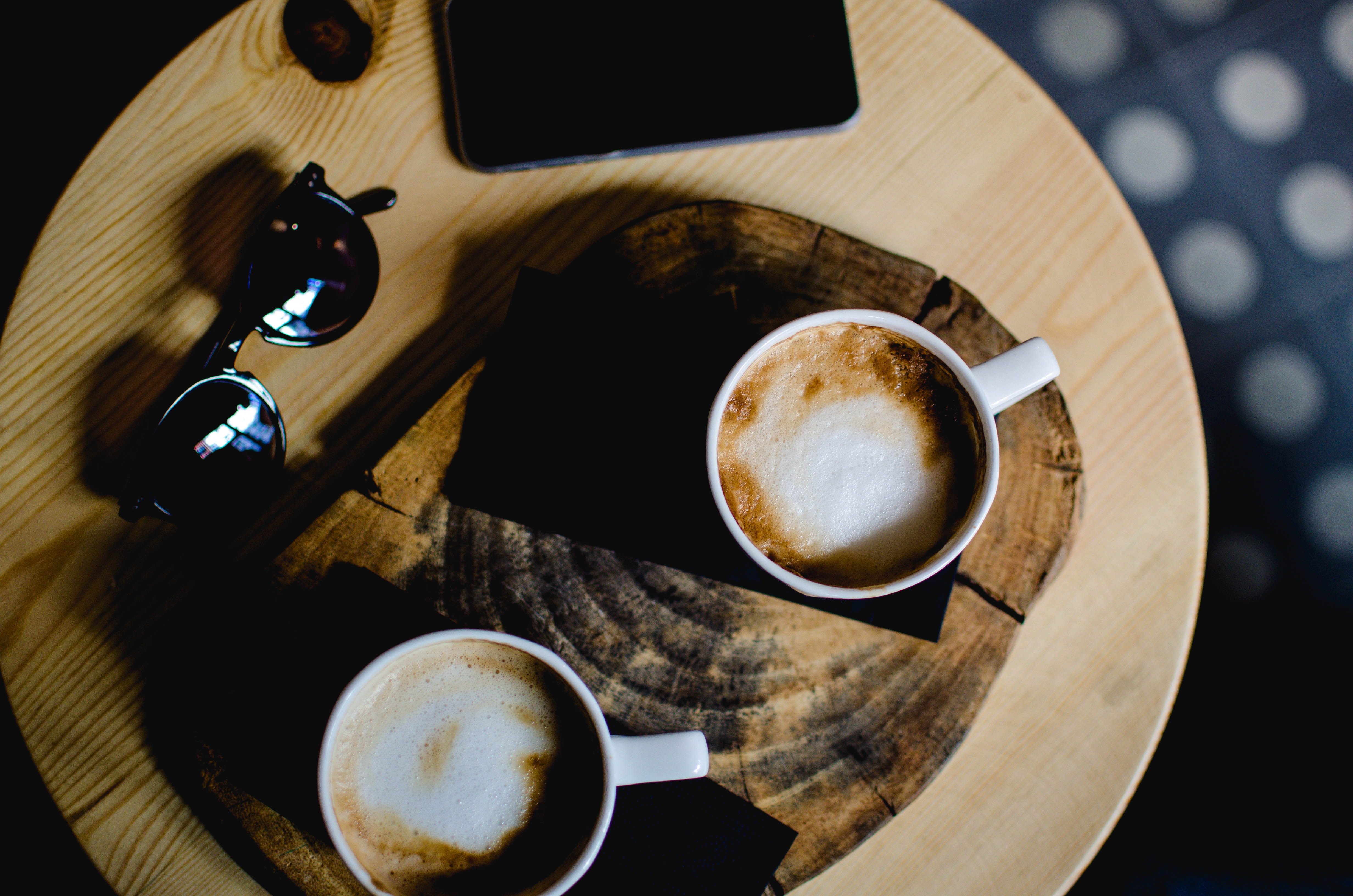 two ceramic cups with cafe latte on wooden table