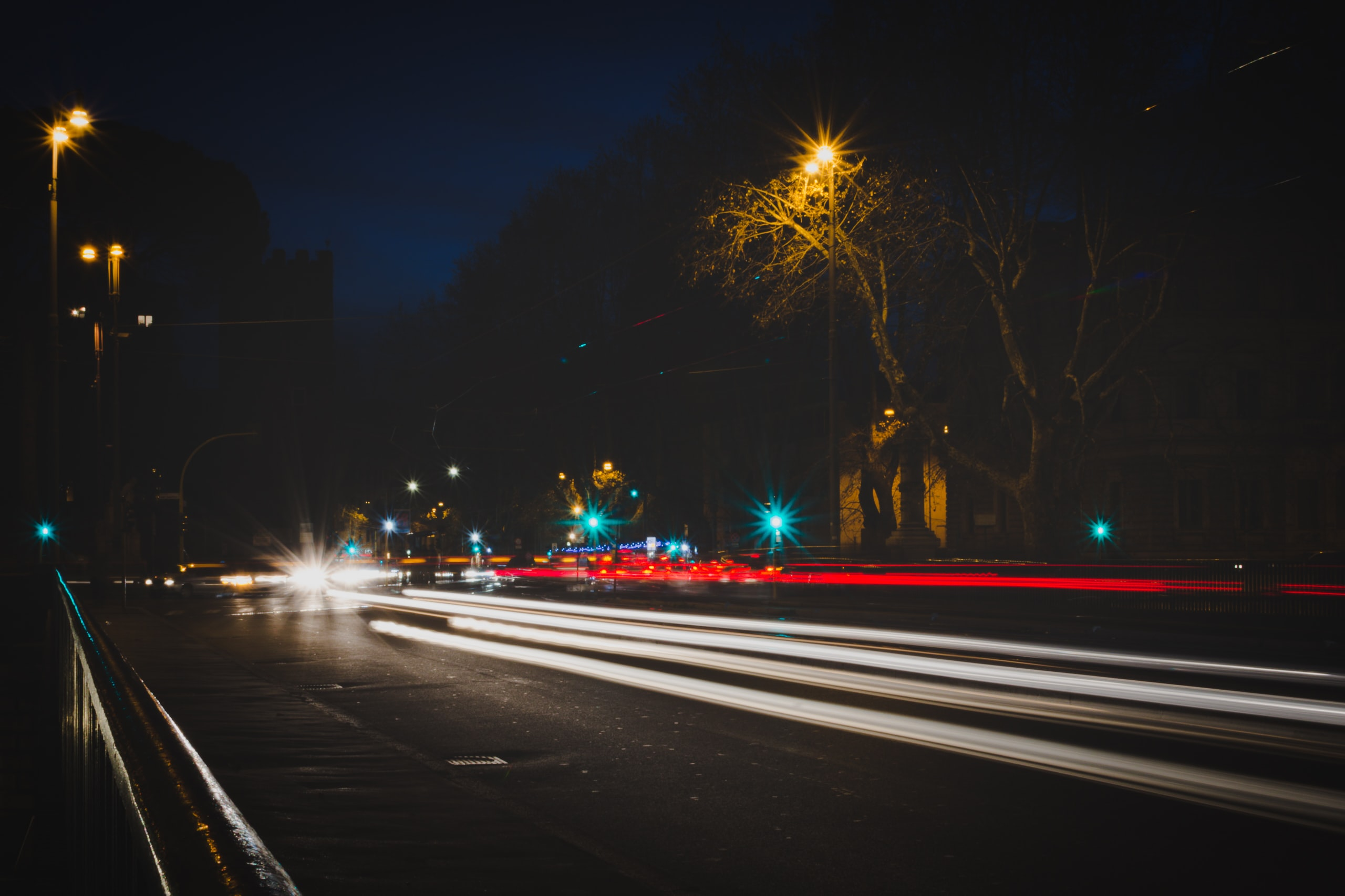 Red and white car light trails at night in the urban area of Rome, Italy.