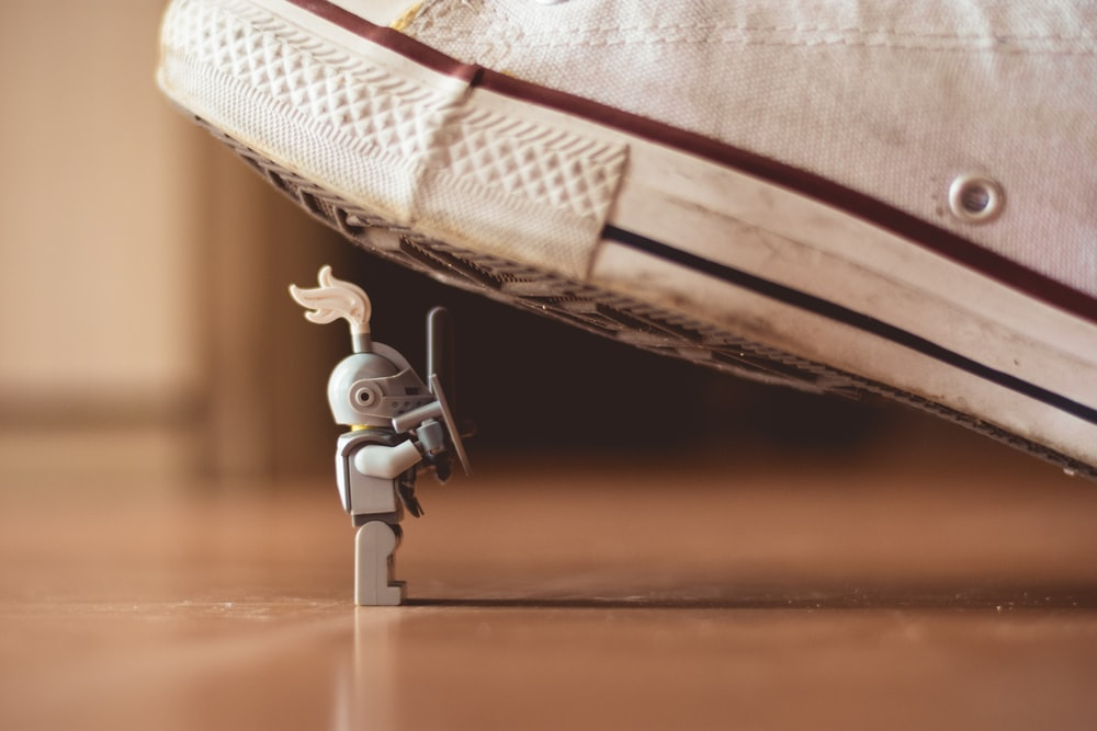 gray mini figure under white sneaker