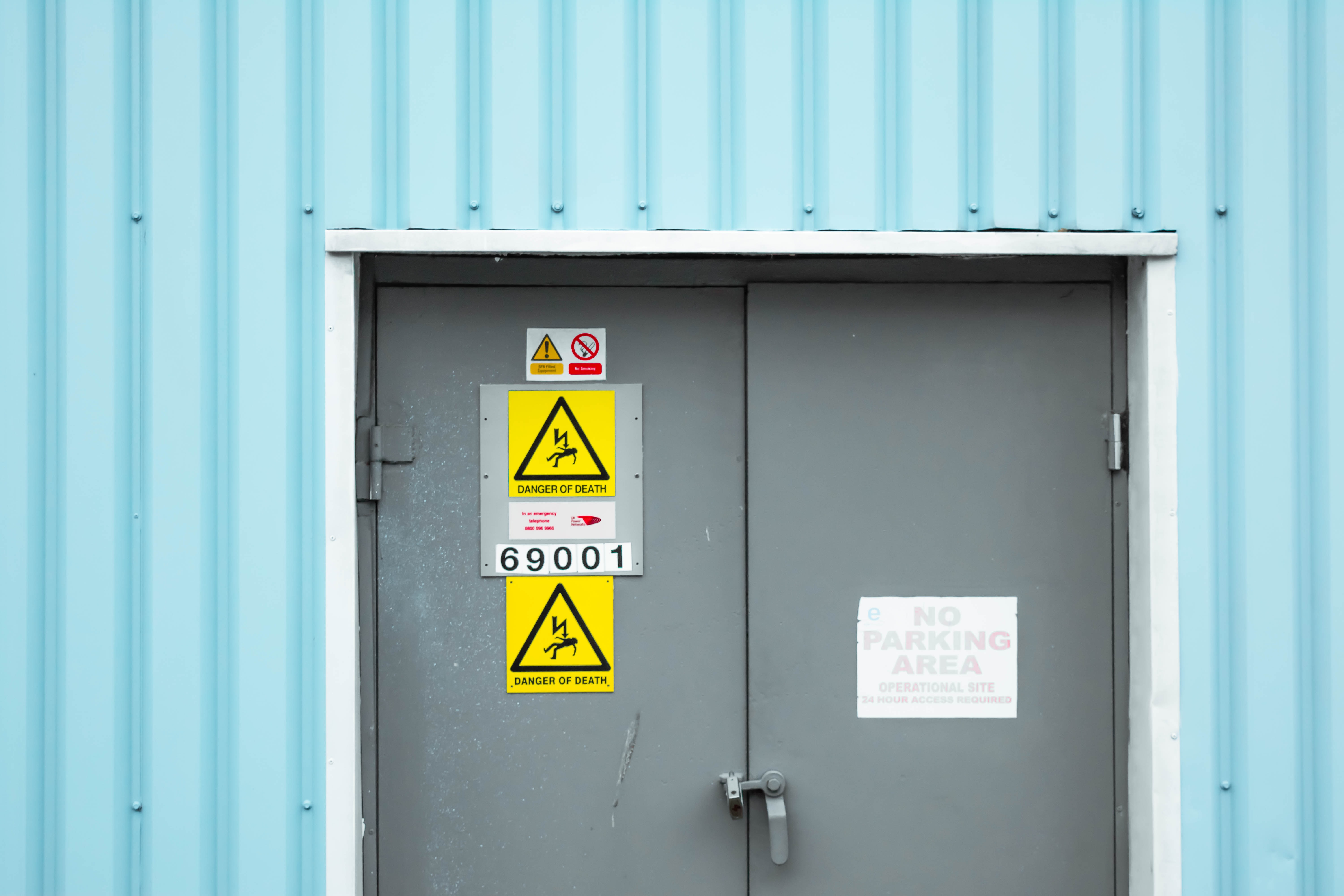 Pastel blue metal wall with grey door and yellow danger of death warning signs, London