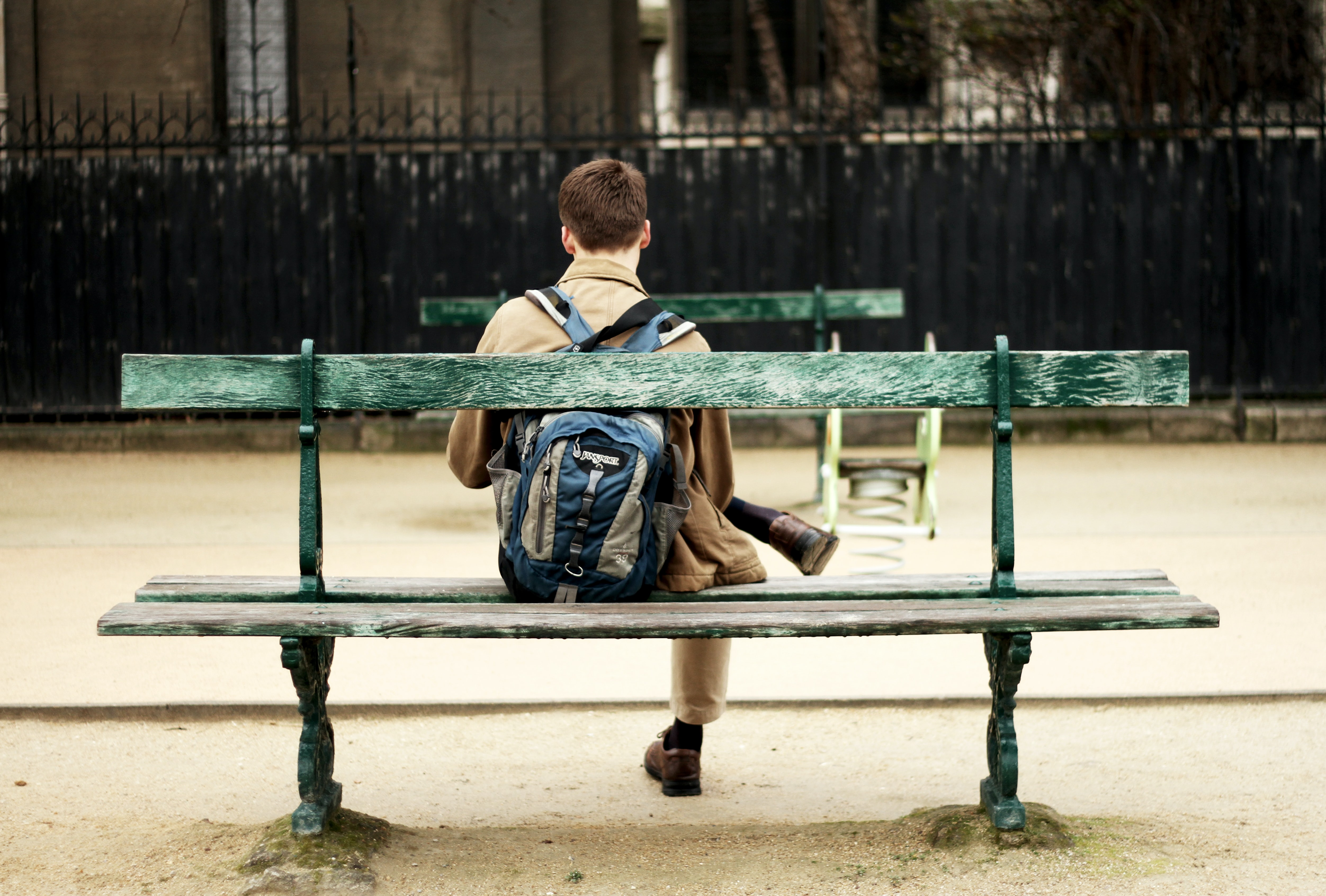 A person in a backpack sits on an outdoor bench, crossing their legs