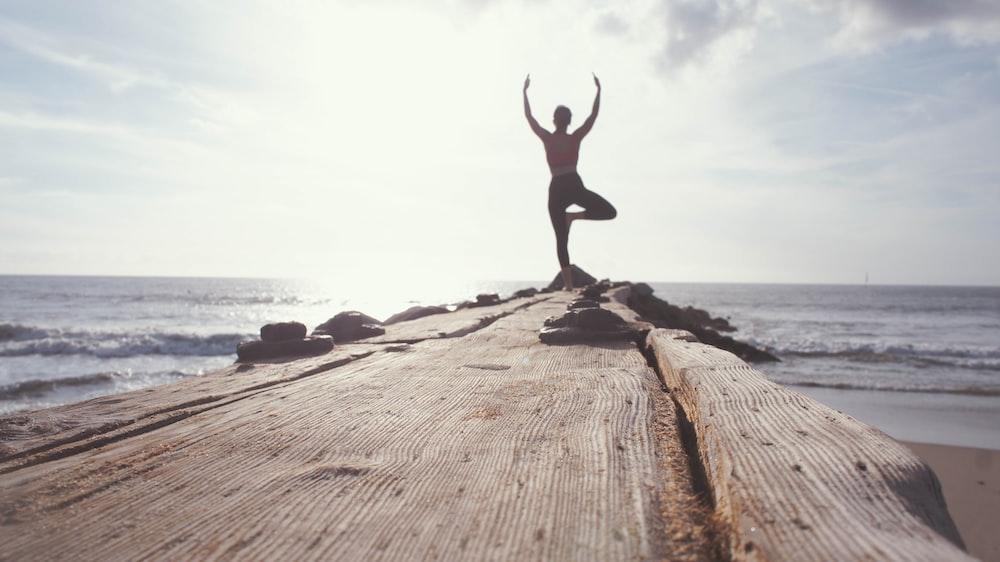 man standing while raising his hands at seashore