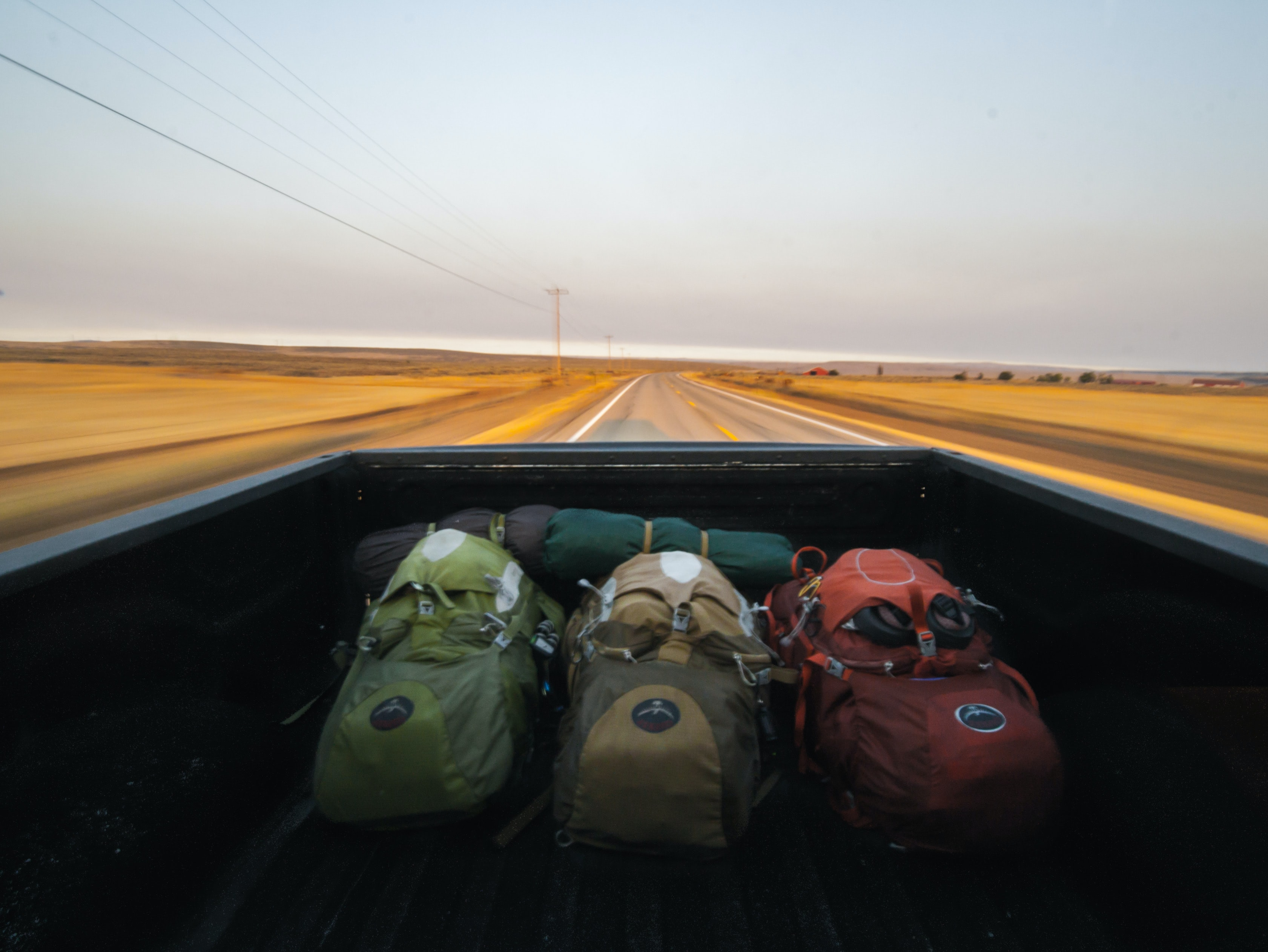 A view from the inside of a cargo area of a pickup truck with three backpacks in it