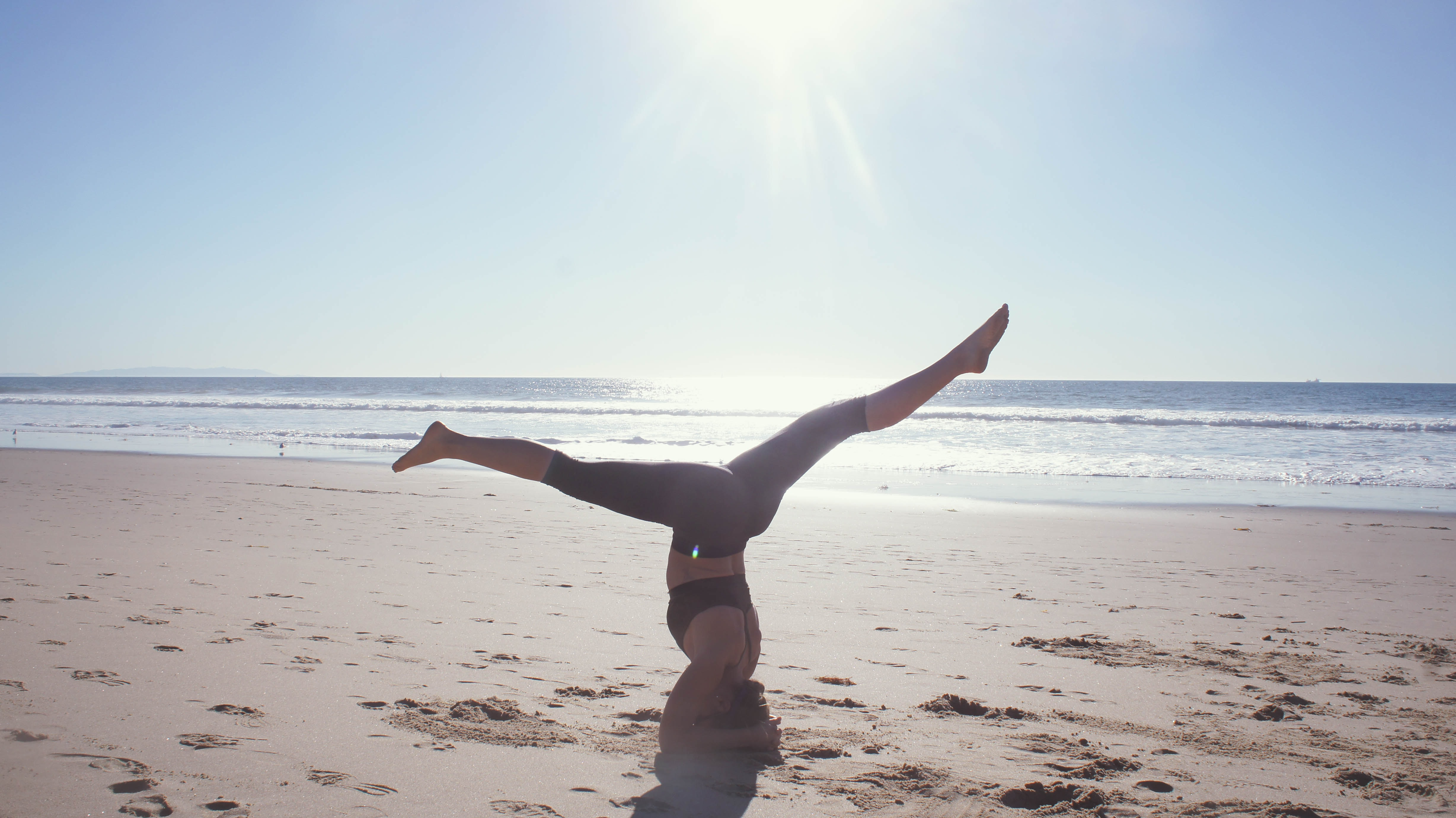 A woman stretching her legs in handstand position on the beach.