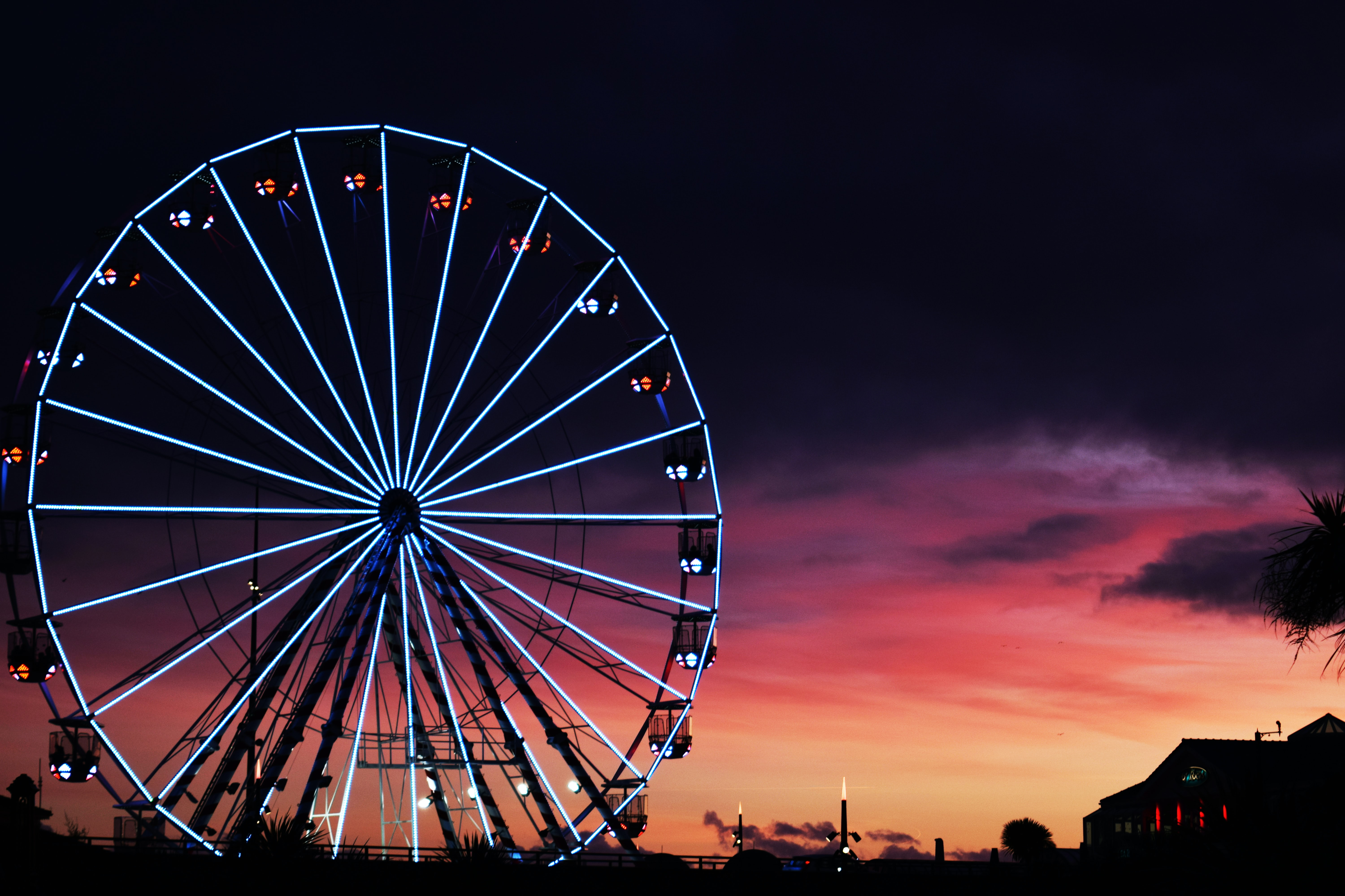 A colourfully illuminated ferris wheel turning in front of a purple and orange sunset in Bournemouth