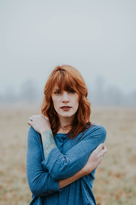 woman in blue raglan shirt shallow focus photography