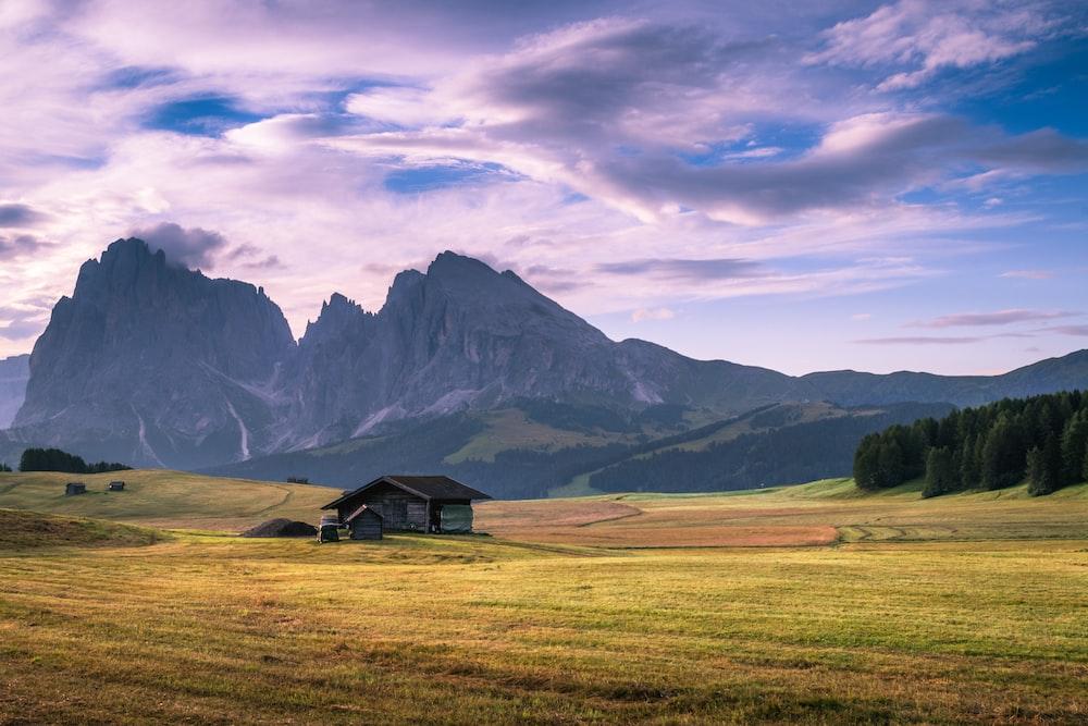 gray wooden house on green plains near mountain range at daytime