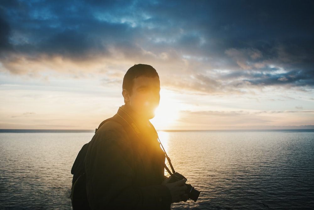 man standing near body of water during daytime