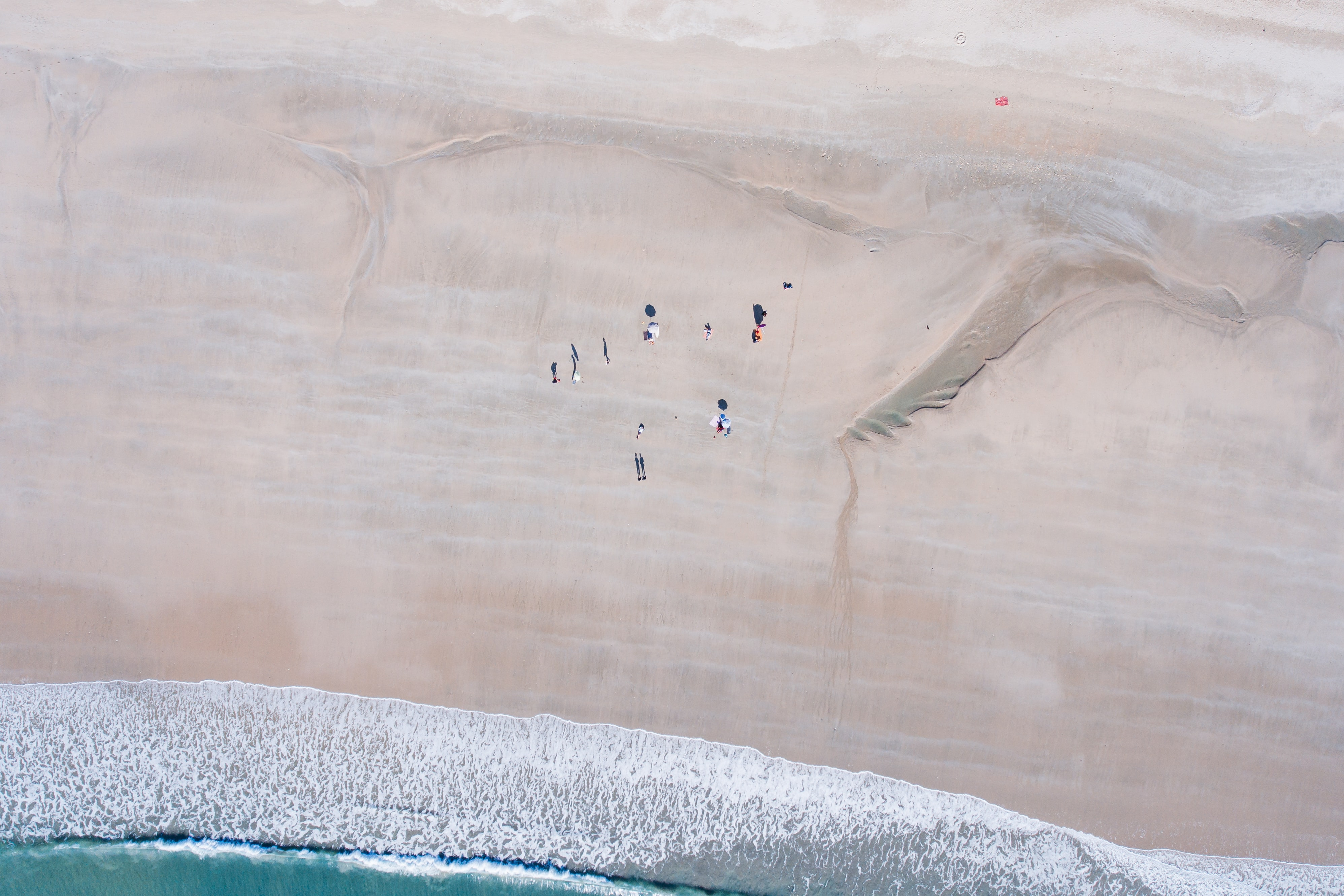 An aerial view of a small group of people on a vast beach