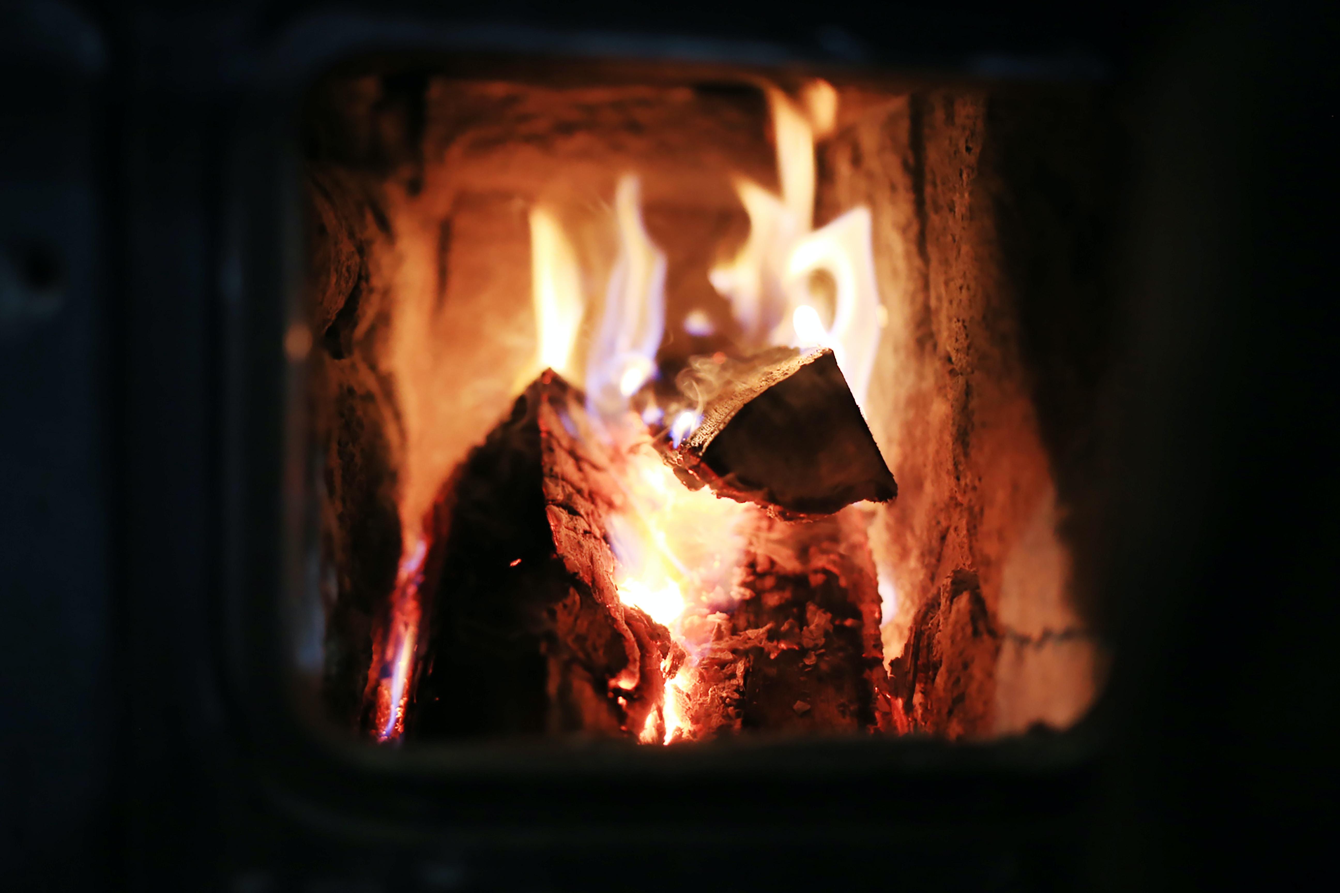 Logs burn in a stone fireplace inside