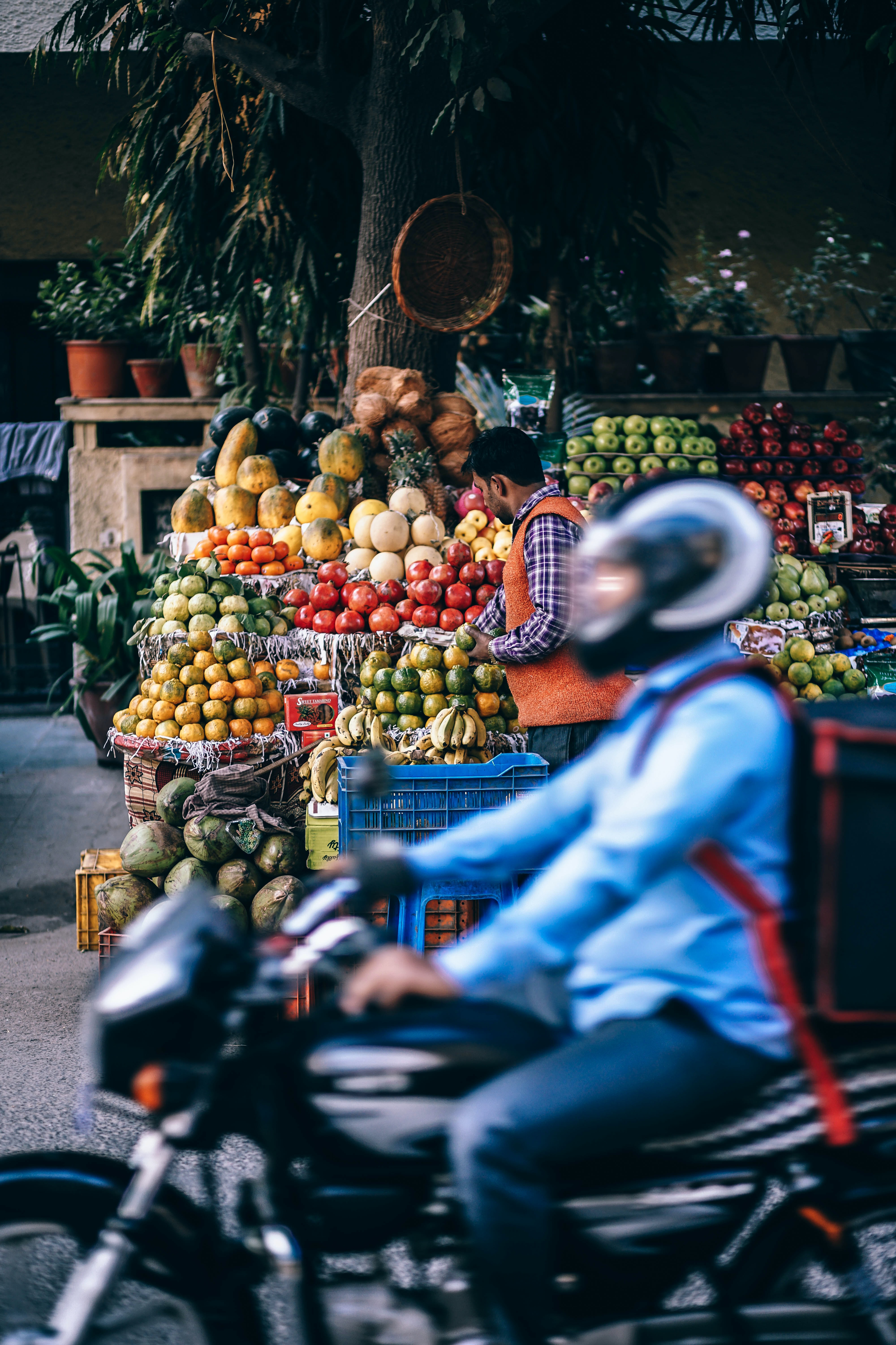 Motorcyclist rides past a street vendor stand with fresh fruits and vegetables