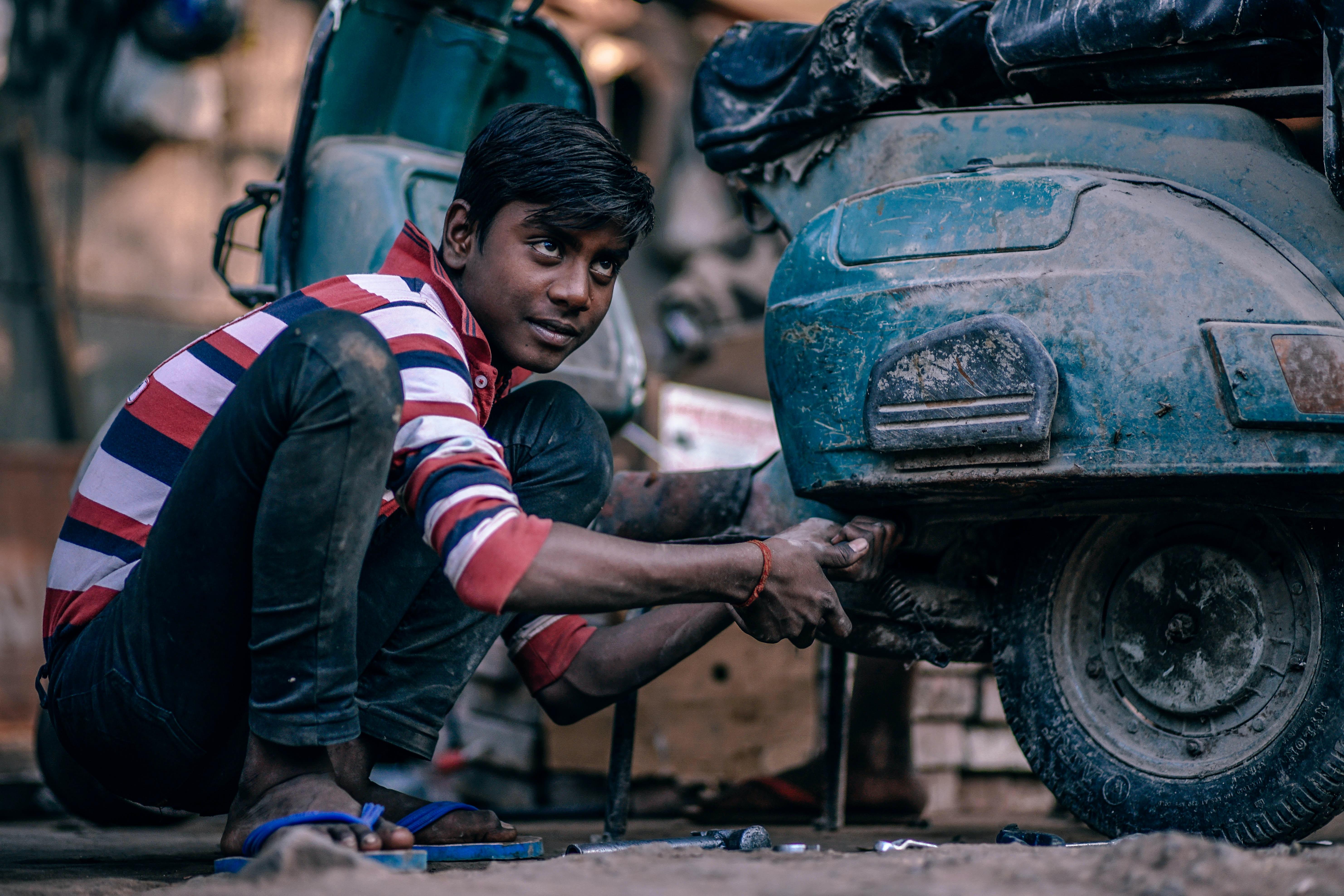man fixing black motorcycle