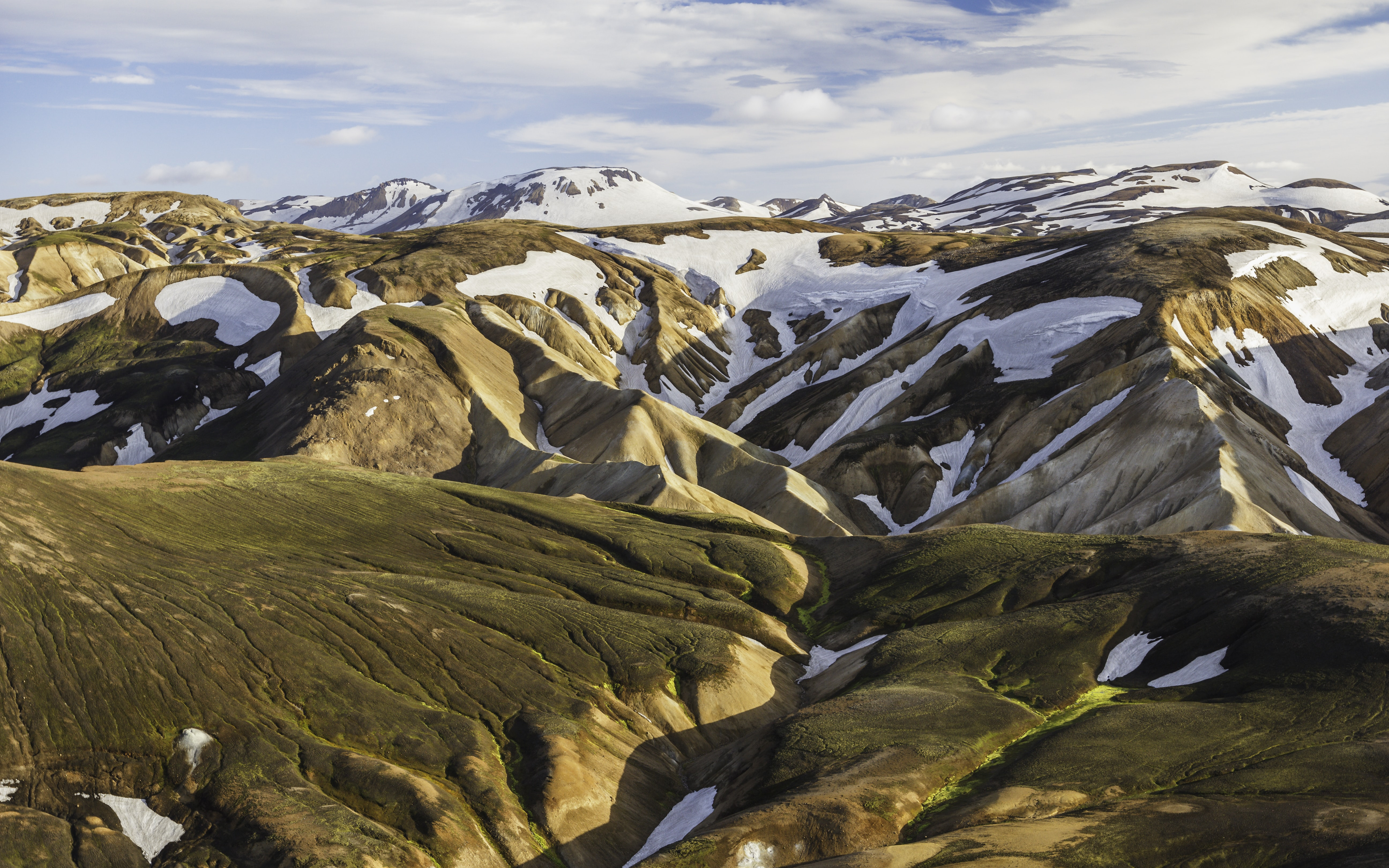 Folded mountain slopes covered with patches of snow in Landmannalaugar