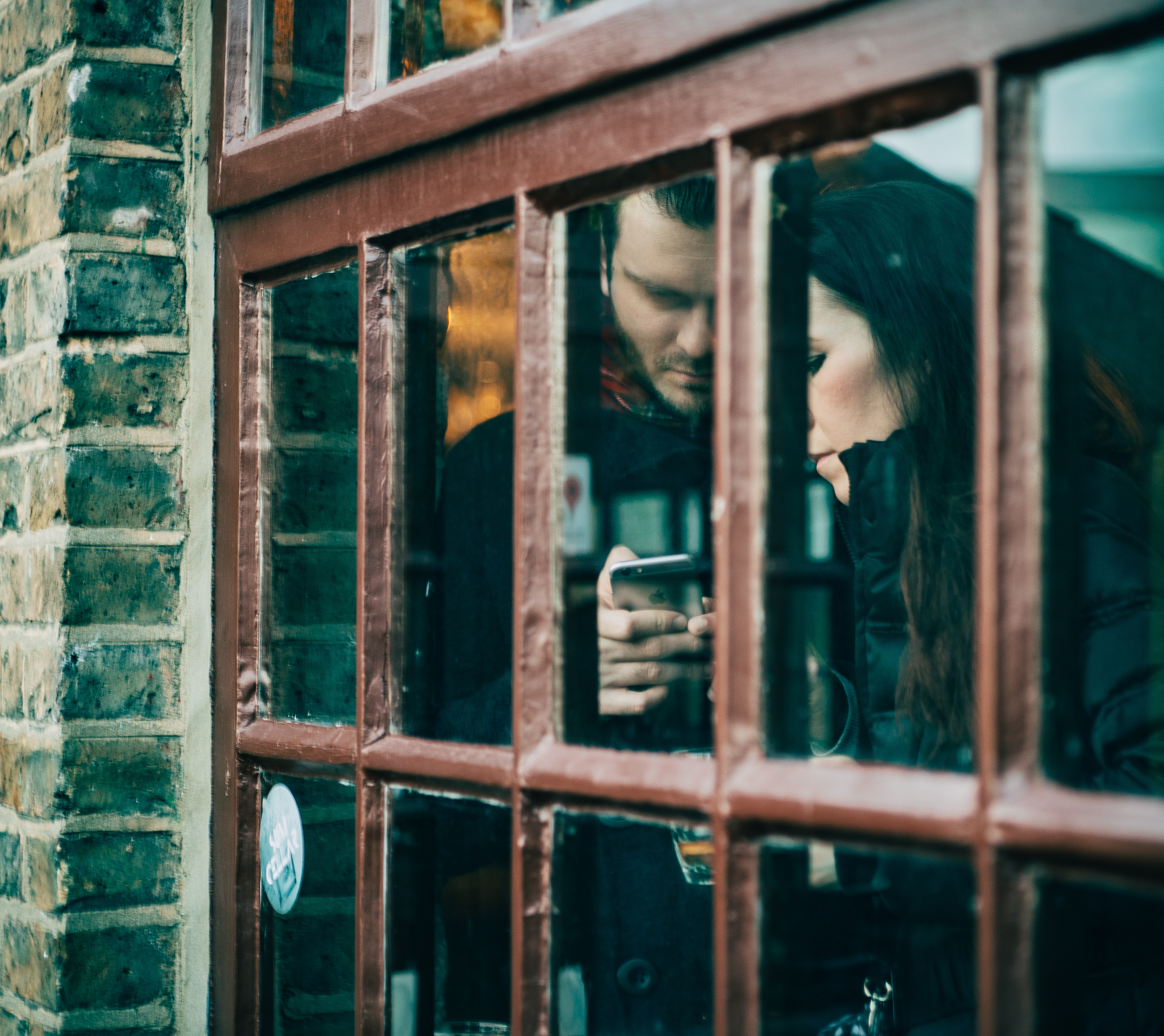 Couple standing indoors by a window in Camden Lock looking at an iPhone