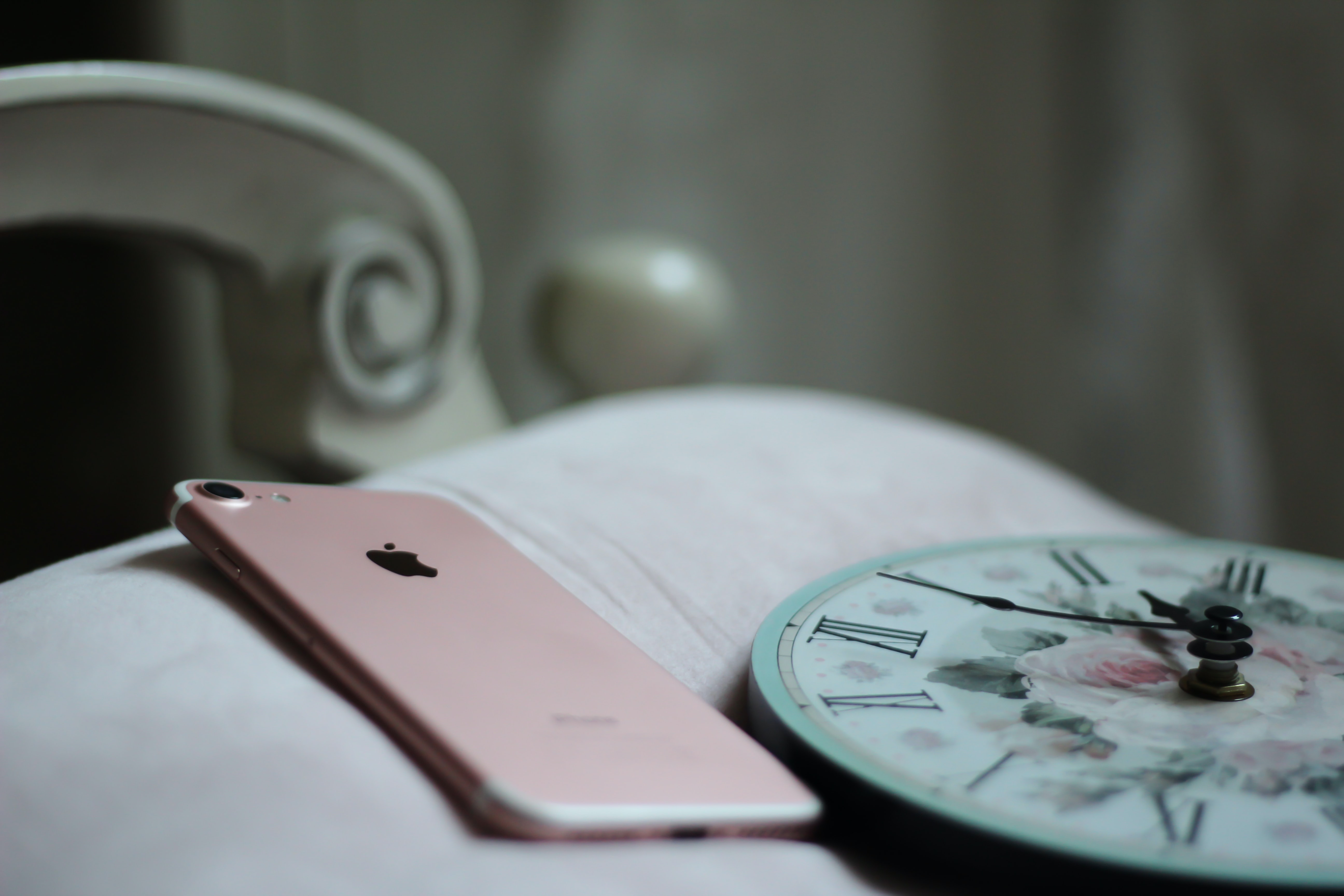 A rose gold iPhone on a pillow next to a clock with a floral pattern