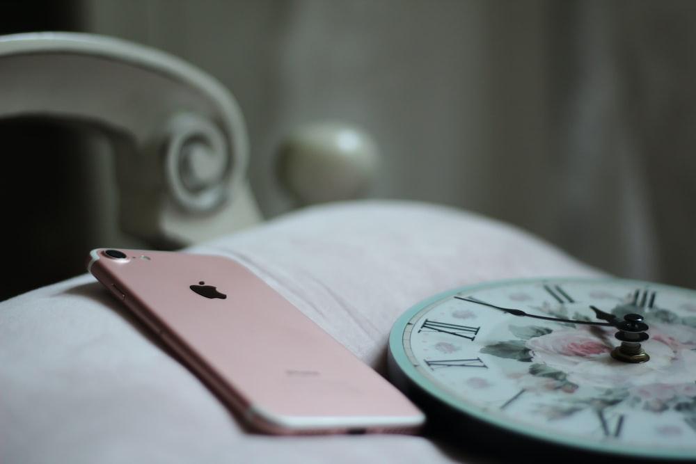 rose gold iPhone 8 near round analog clock