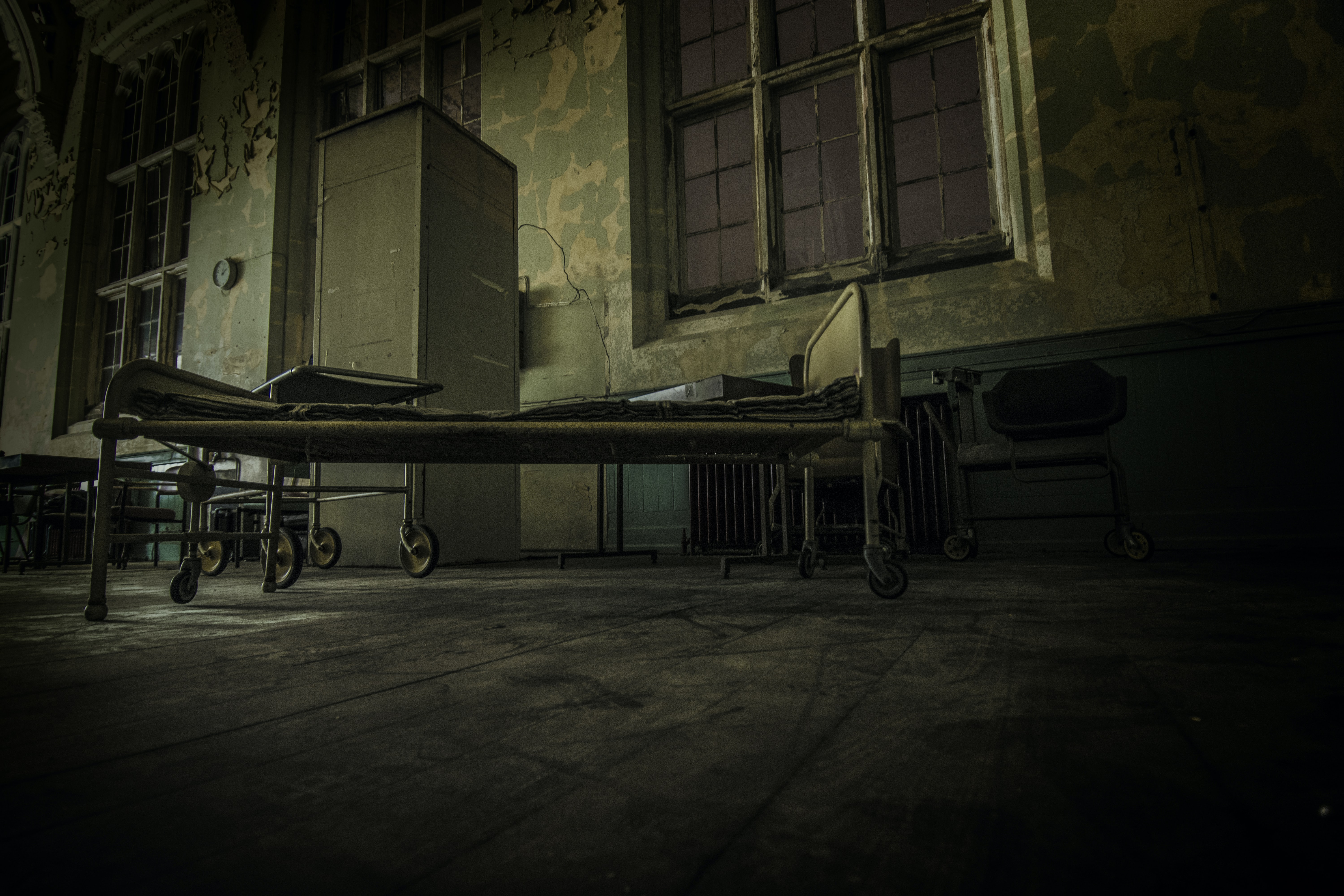 A rundown hospital room with hospital beds and a cabinet in the United Kingdom.