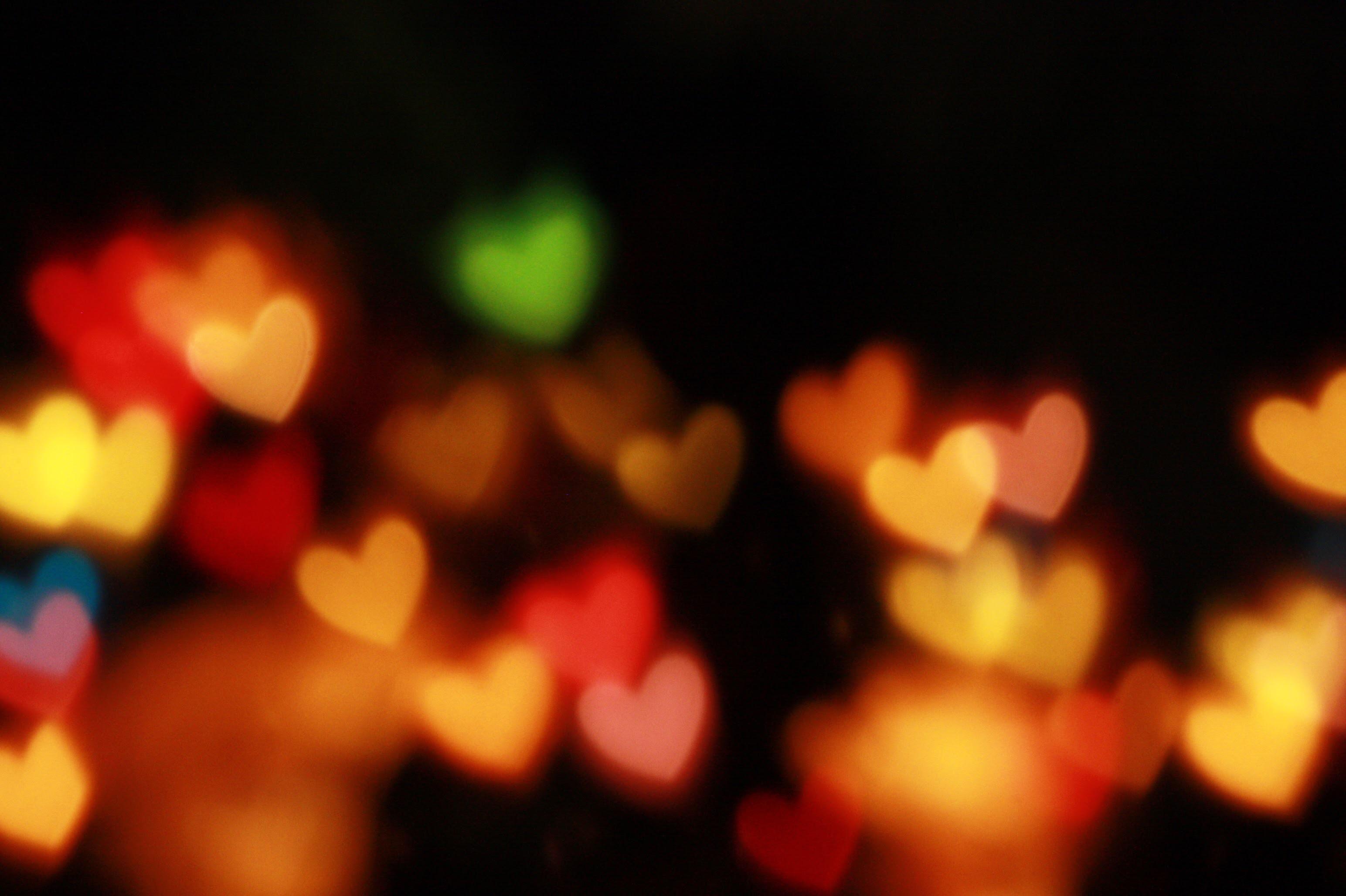 Illuminated multi-colored hearts against a black backdrop