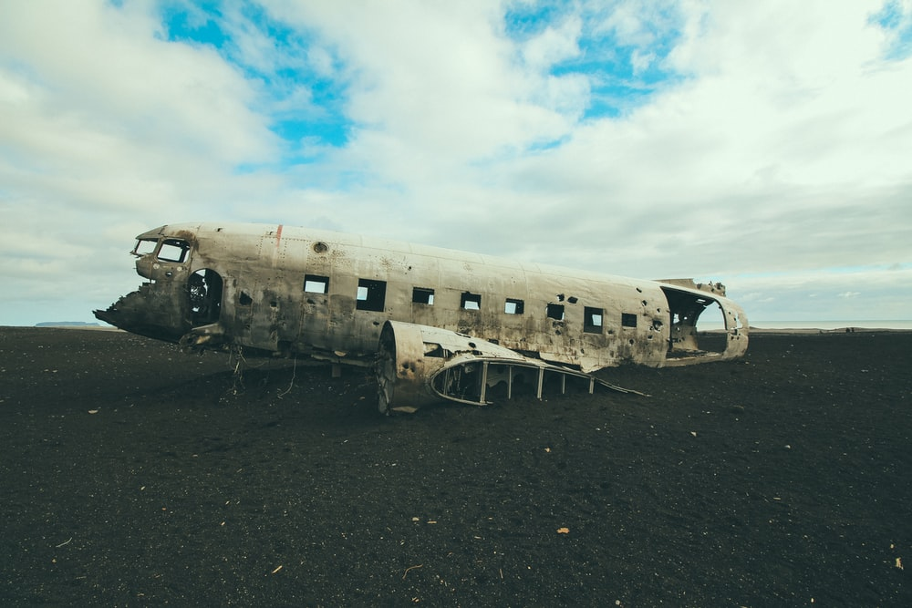 photo of abandoned plane under blue cloudy sky