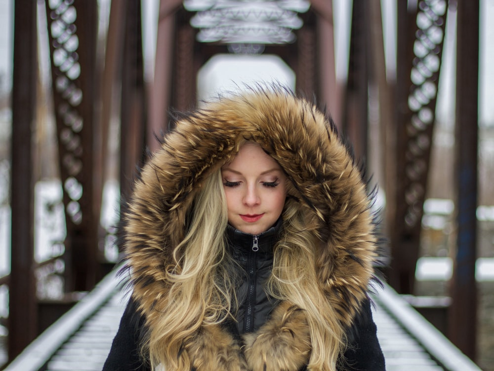 woman wearing brown fur-lined hoodie standing on the bridge during daytime photography