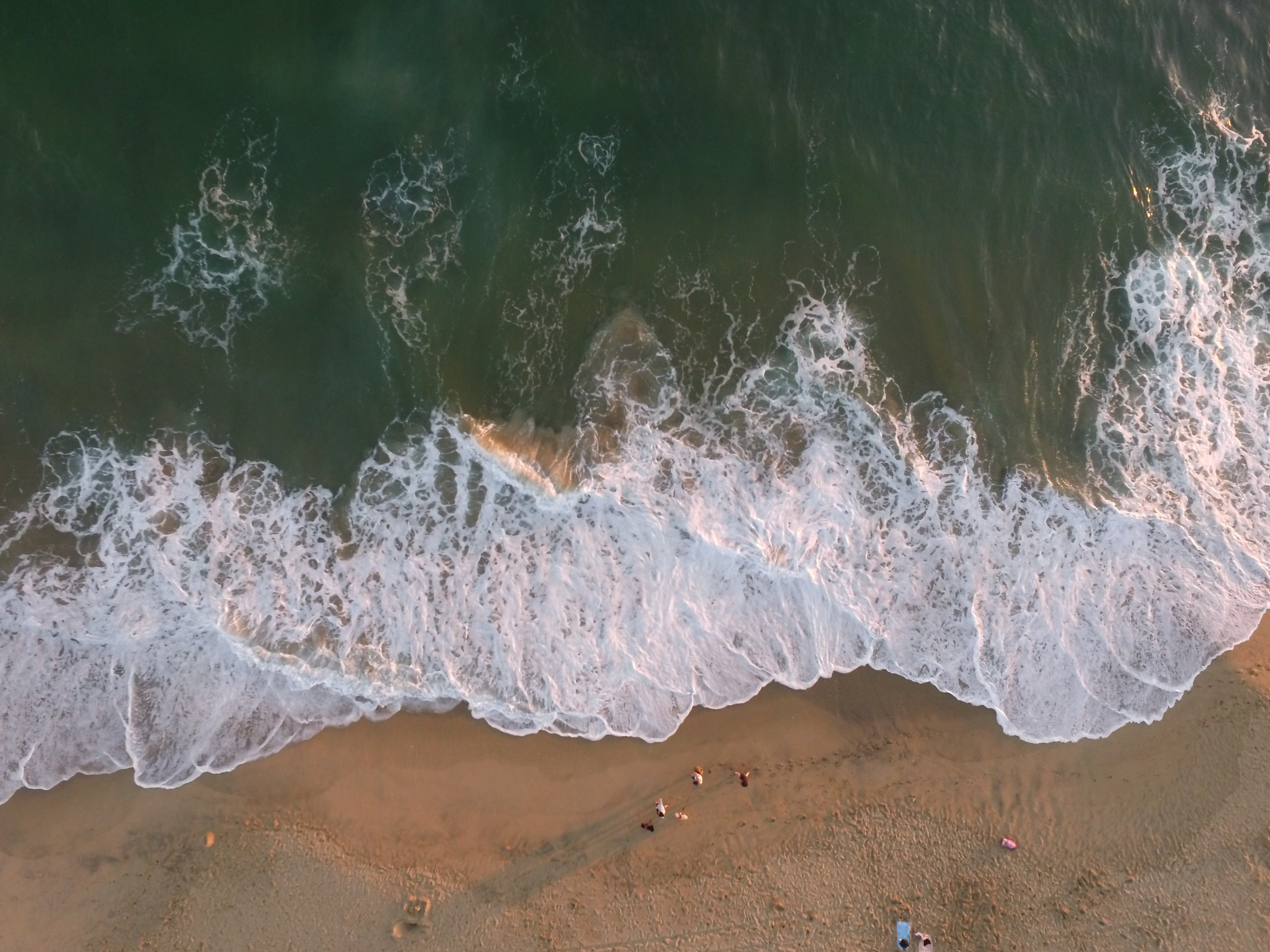 Drone aerial view of the ocean waves washing on the sand beach in Huntington Beach, California, United States