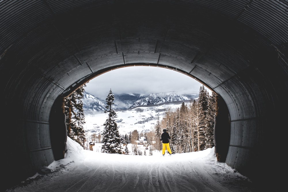 A person passing along a tunnel covering snow in Telluride, Colorado