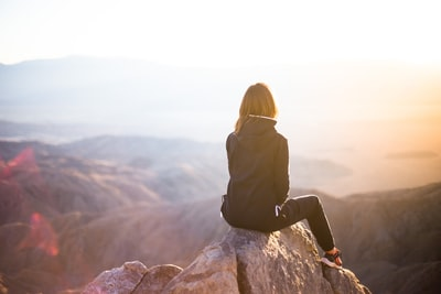 person sitting on top of gray rock overlooking mountain during daytime lifestyle teams background