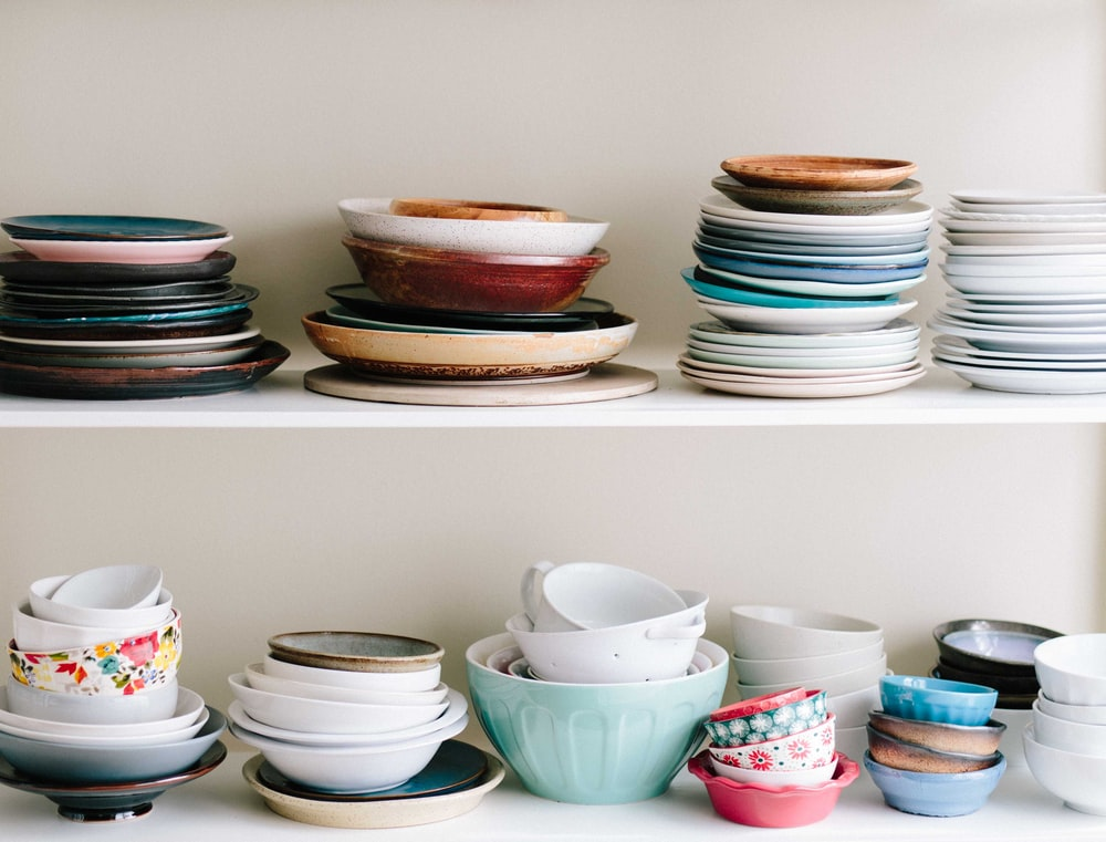 assorted-color ceramic bowls and saucers lot on white wooden shelves