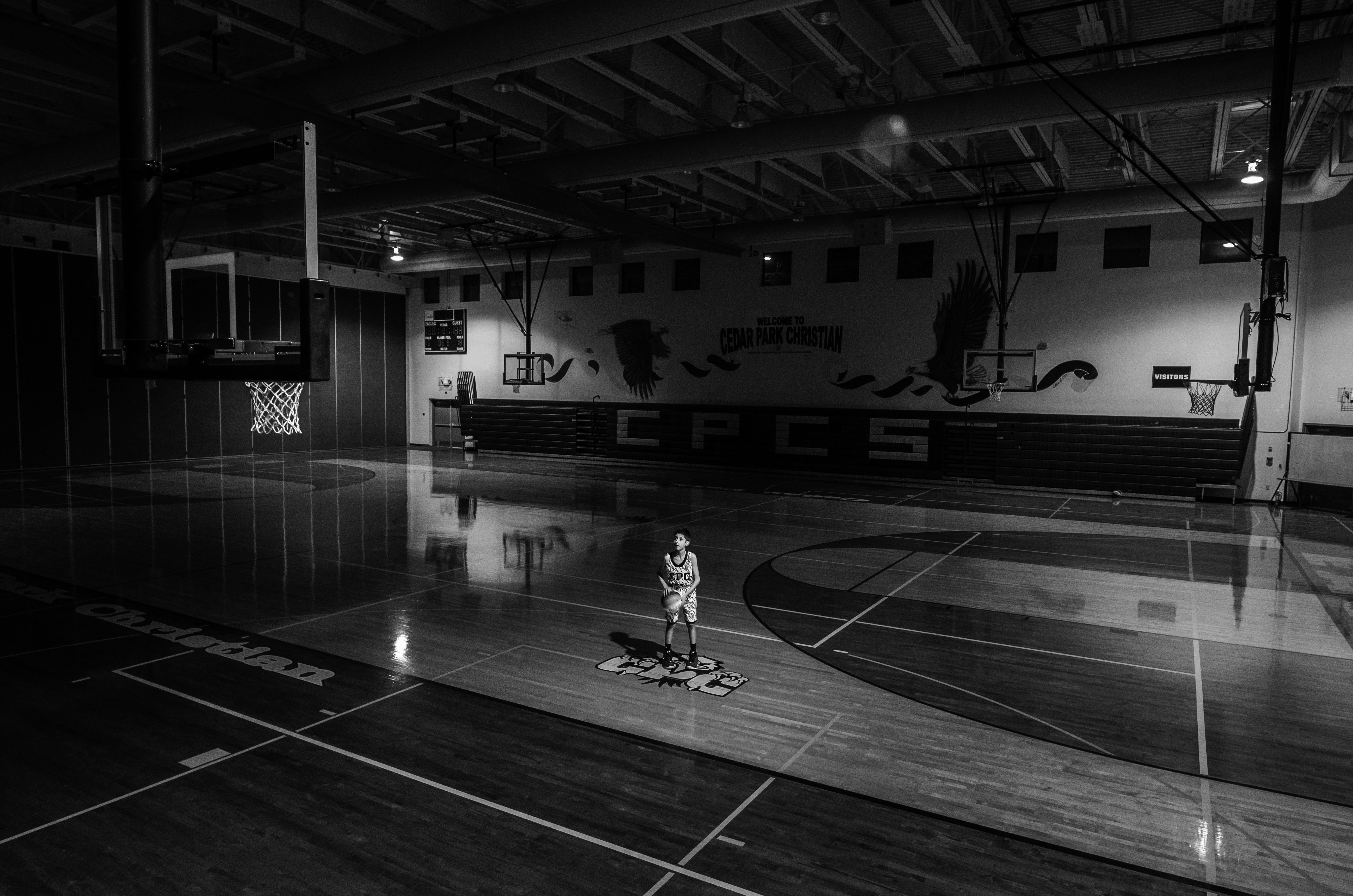 grayscale photo of boy holding ball standing on basketball court
