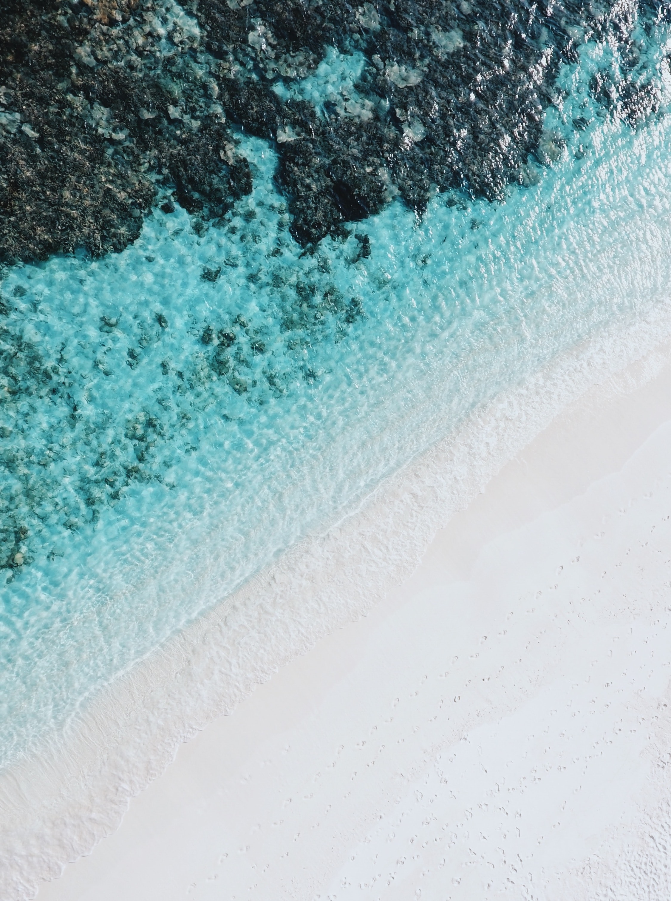 Drone view of a white sandy beach by the clear ocean in Bathalaa