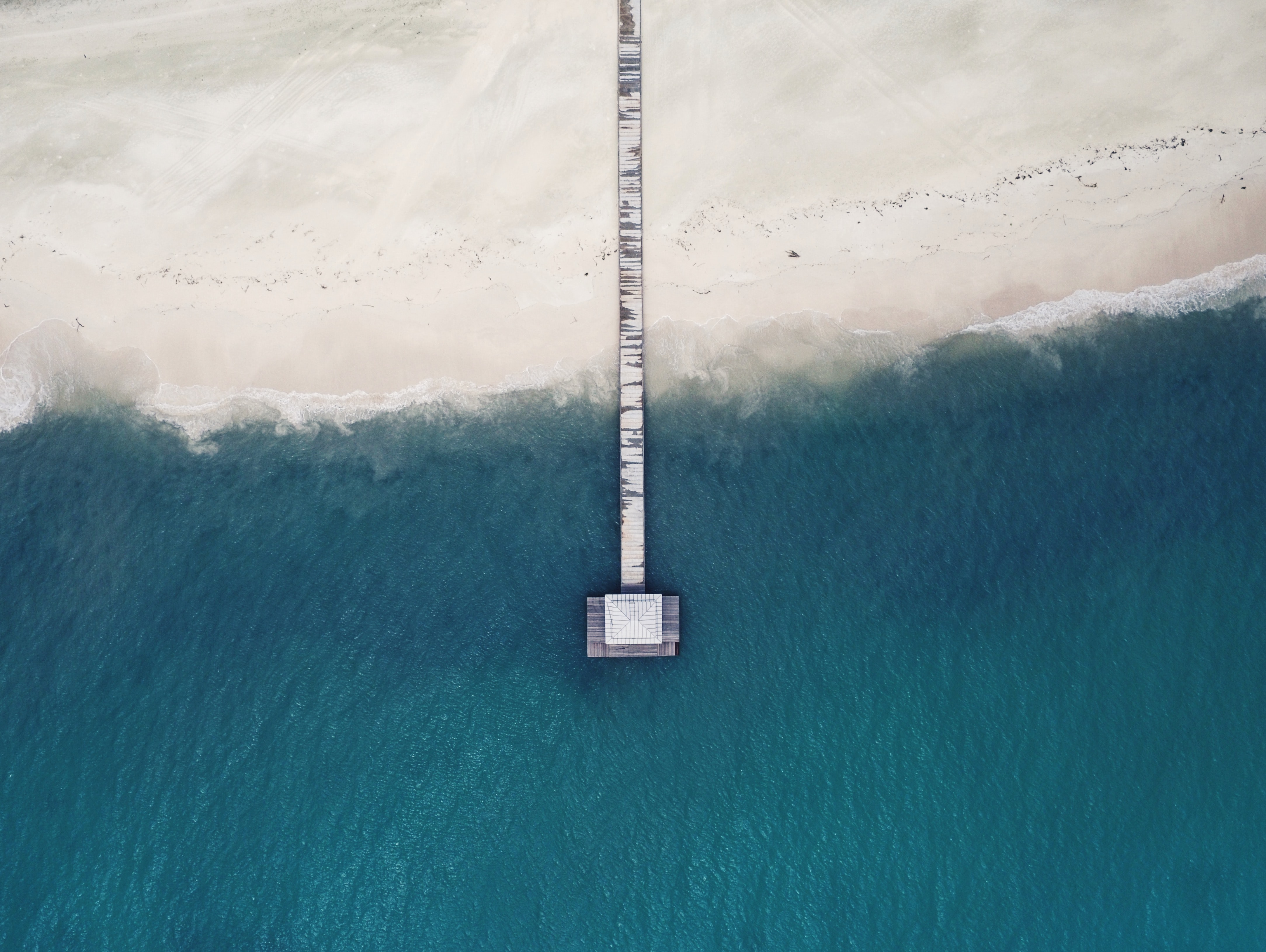 Drone aerial view of a long wooden pier at the sand beach in Hon'daafushi