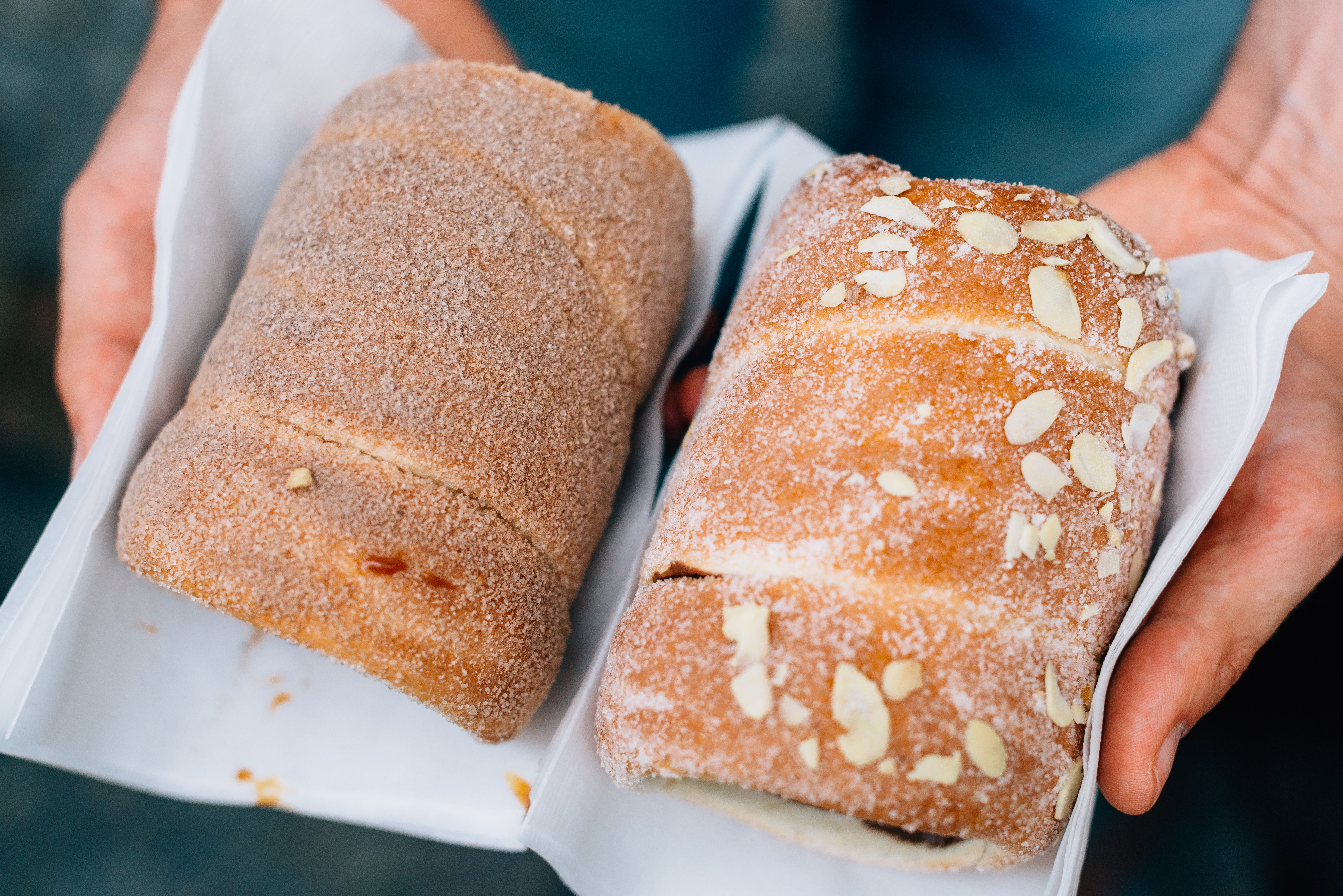 Hands hold two loaves of freshly baked sweet bread