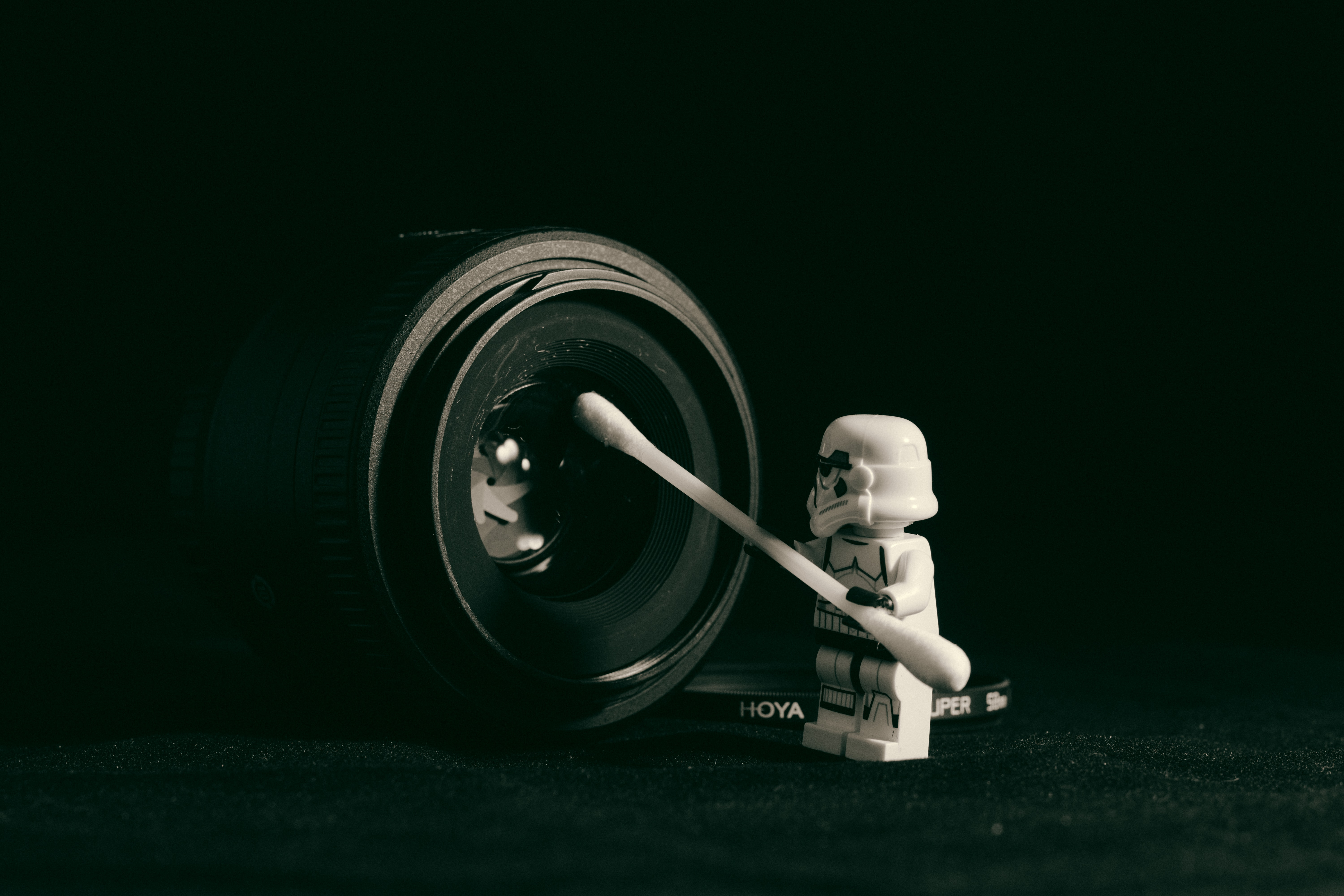 White toy stormtrooper figure with q-tip cleaning black camera lens, Curitiba