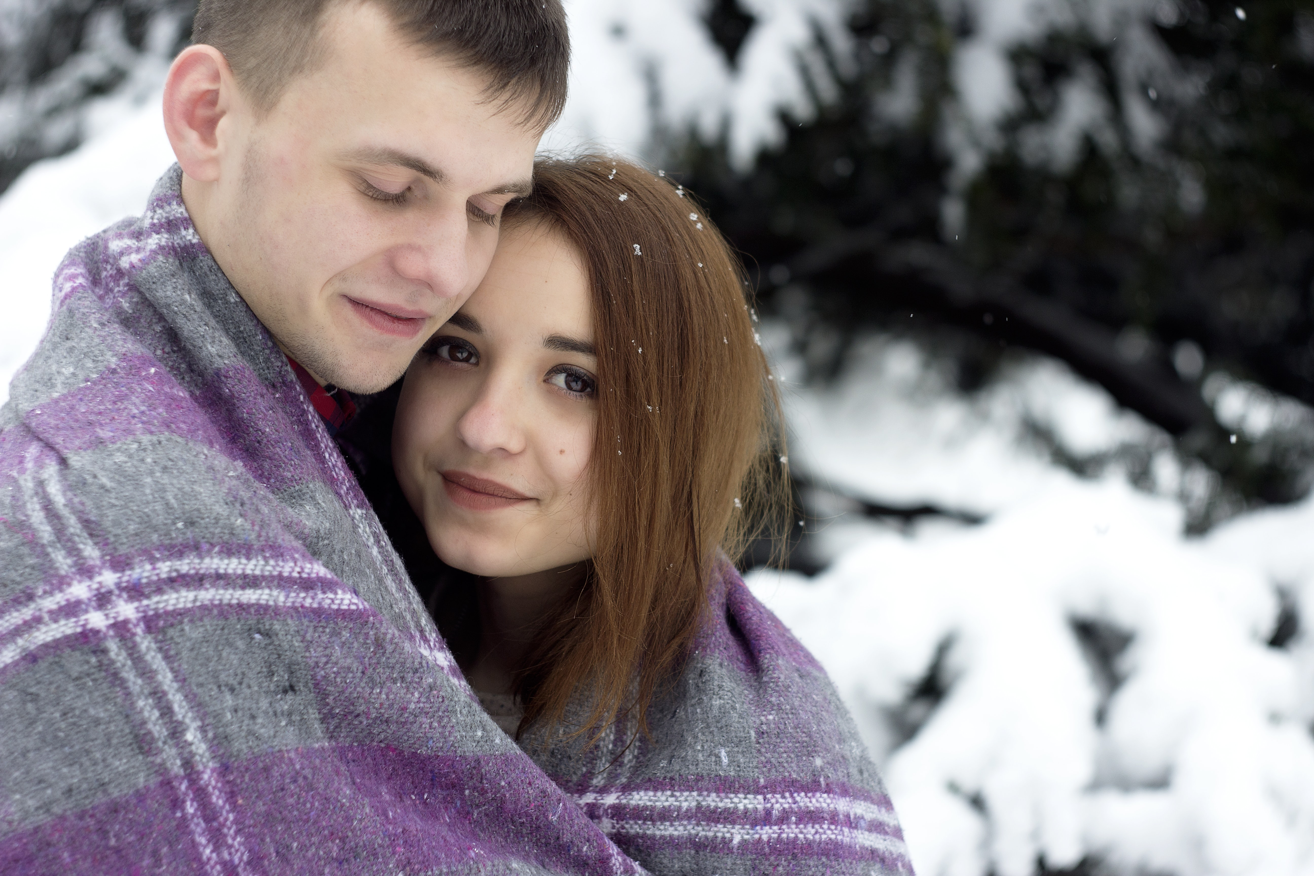 A happy man and woman wrapped in a blanket together next to a snow covered tree.