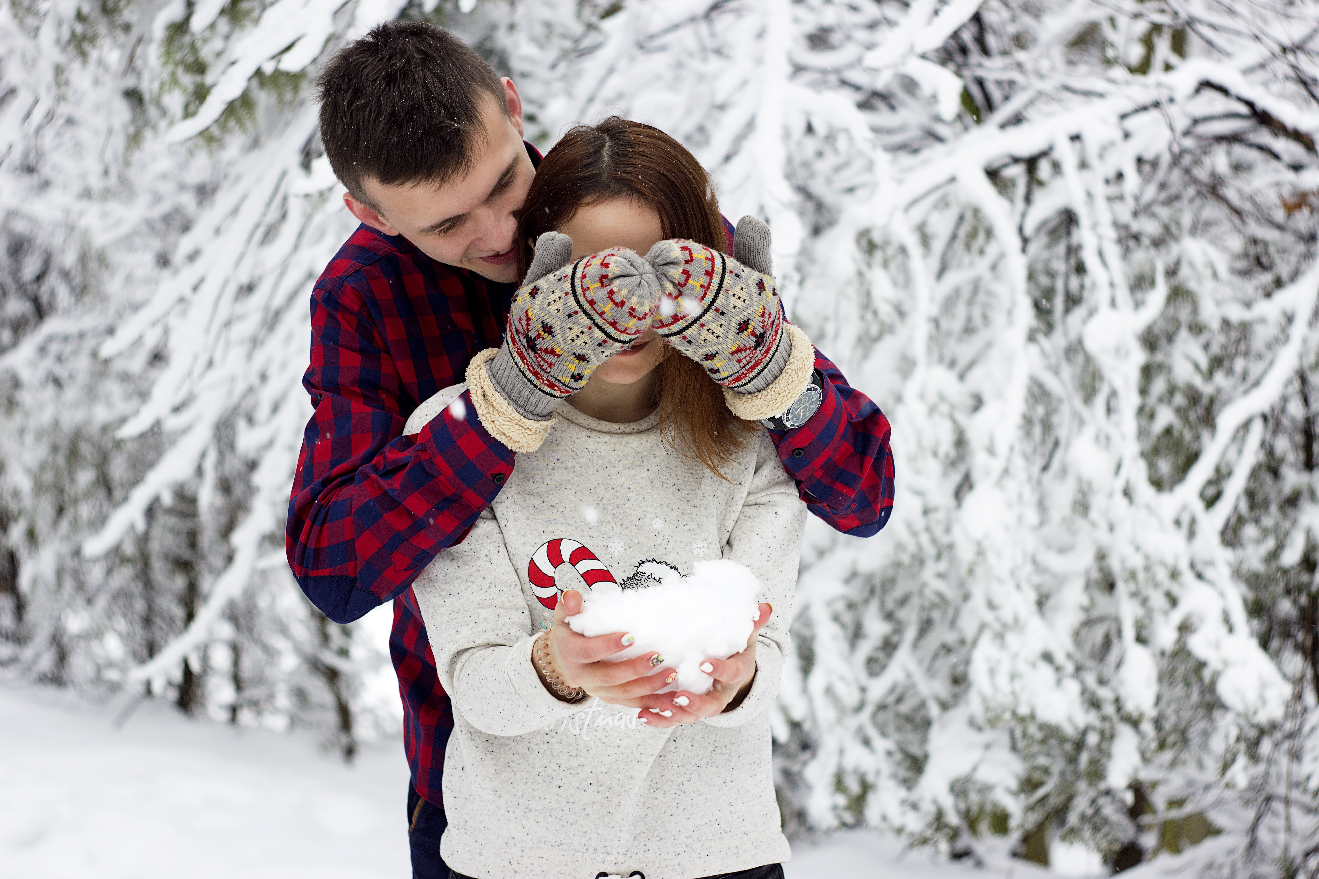 man in red and blue gingham sweatshirt covering eye of girl in gray sweatshirt while holding iceball