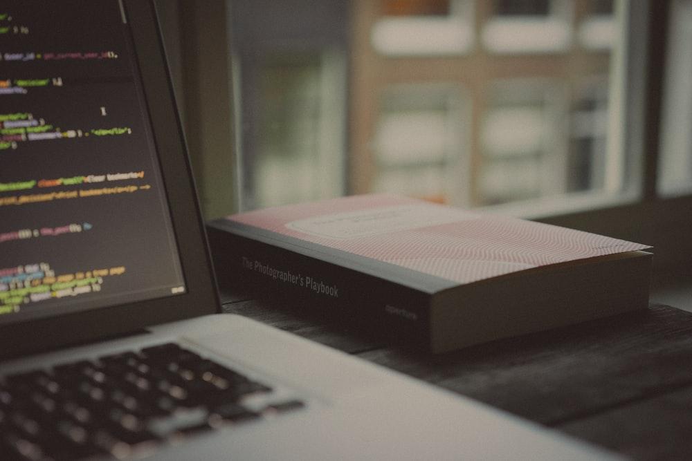 book beside laptop computer