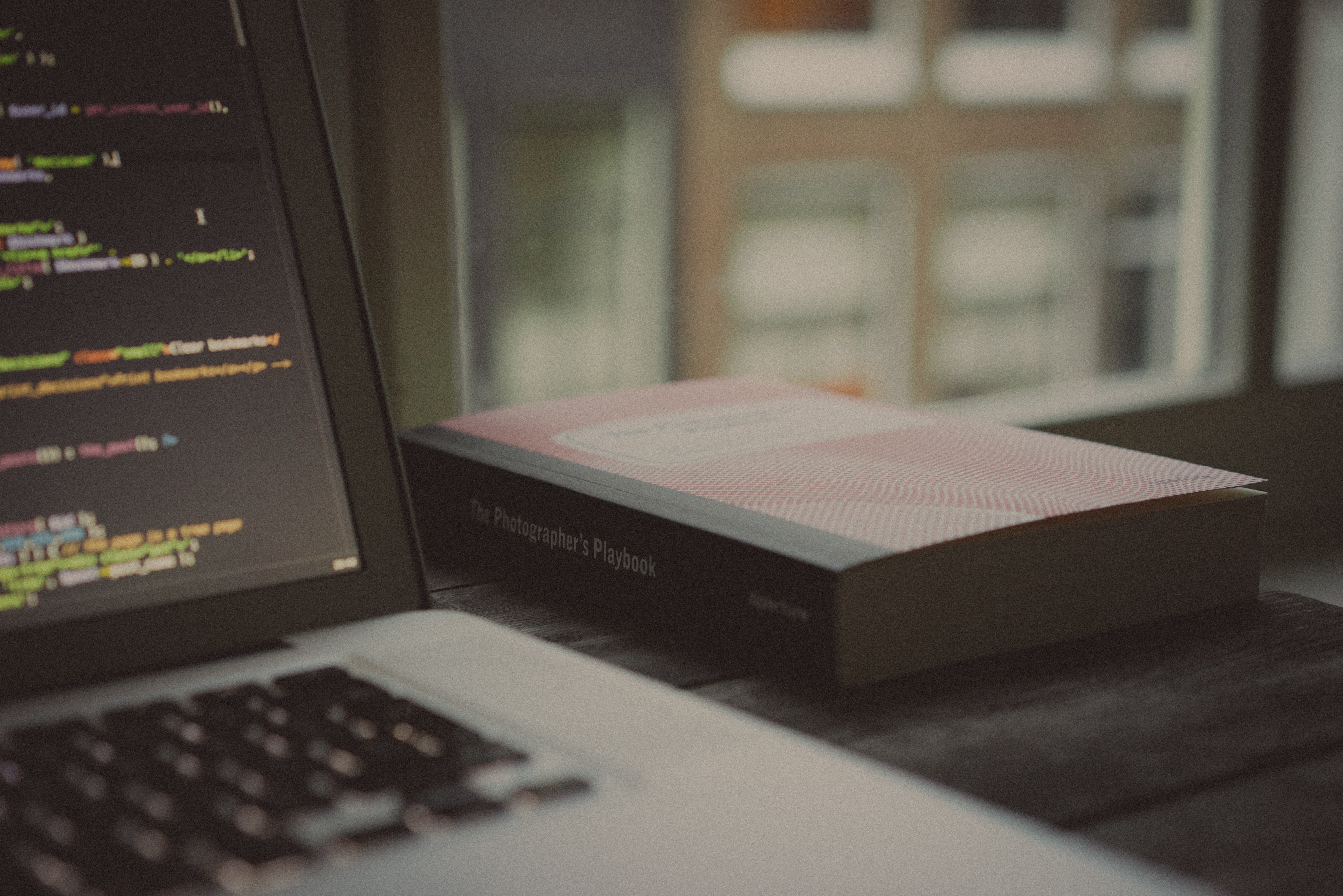 """""""The Photographer's Playbook"""" on a desk next to a laptop with lines of code on its screen"""