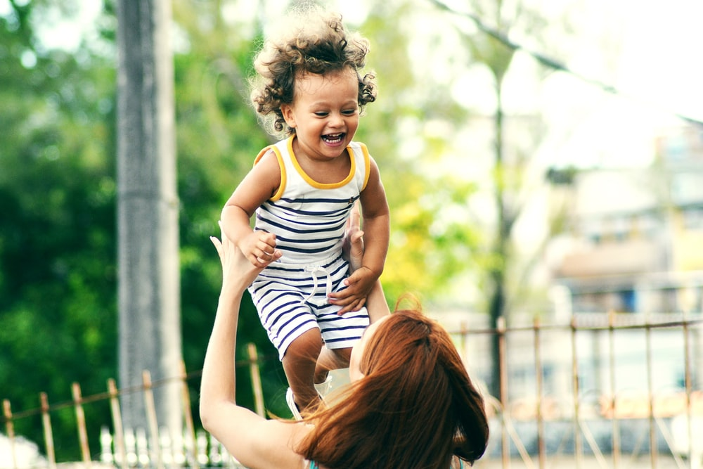selective focus photo of woman lifting child during daytime