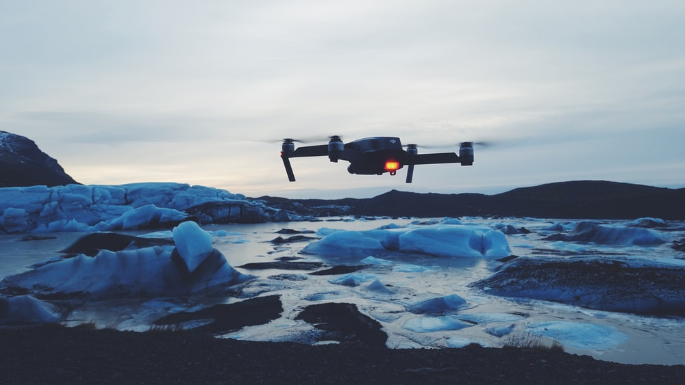 drone flying on body of water