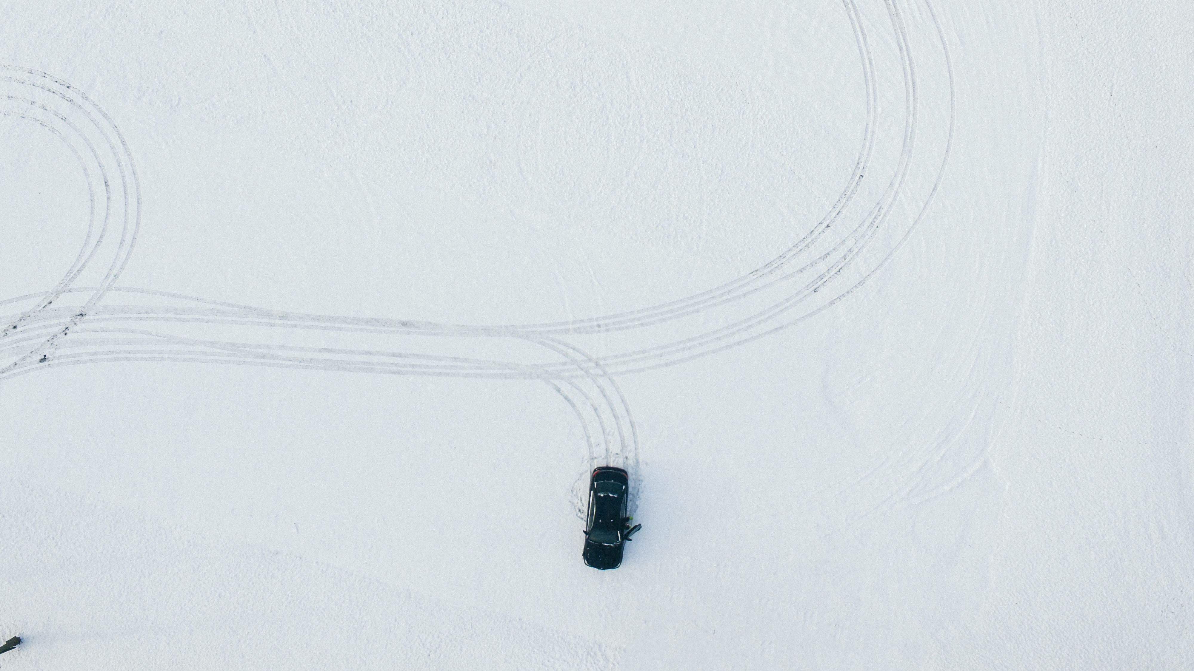 A drone shot of a car leaving tire marks in the snow