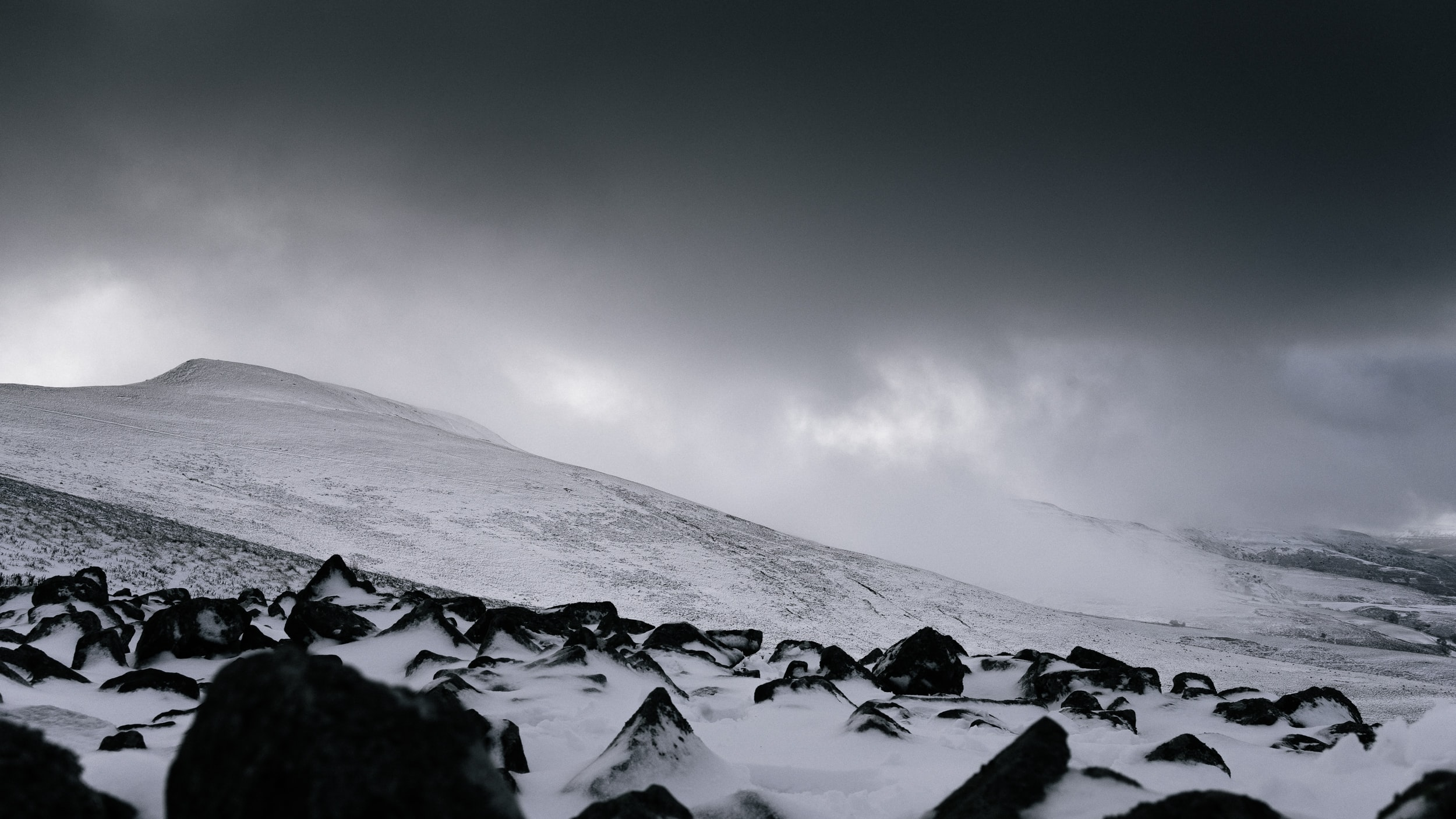 A night time shot of a dark clouded sky above a sloped hill in Brecon, Wales
