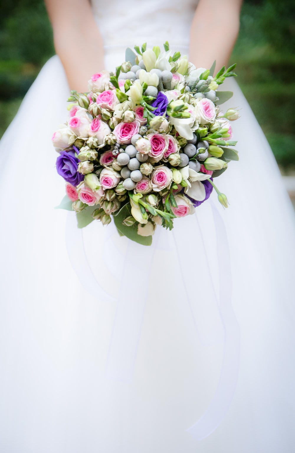 woman holding white and pink flower bouquet