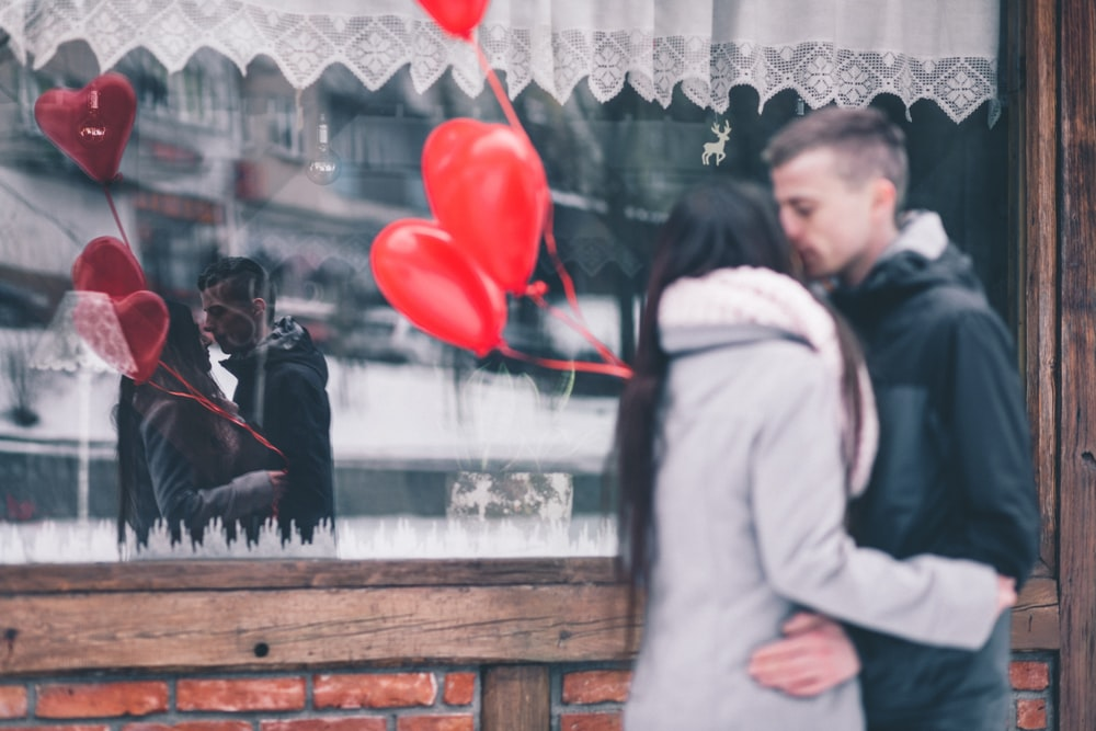 A young man and woman's romantic embrace reflected in a shop window in winter