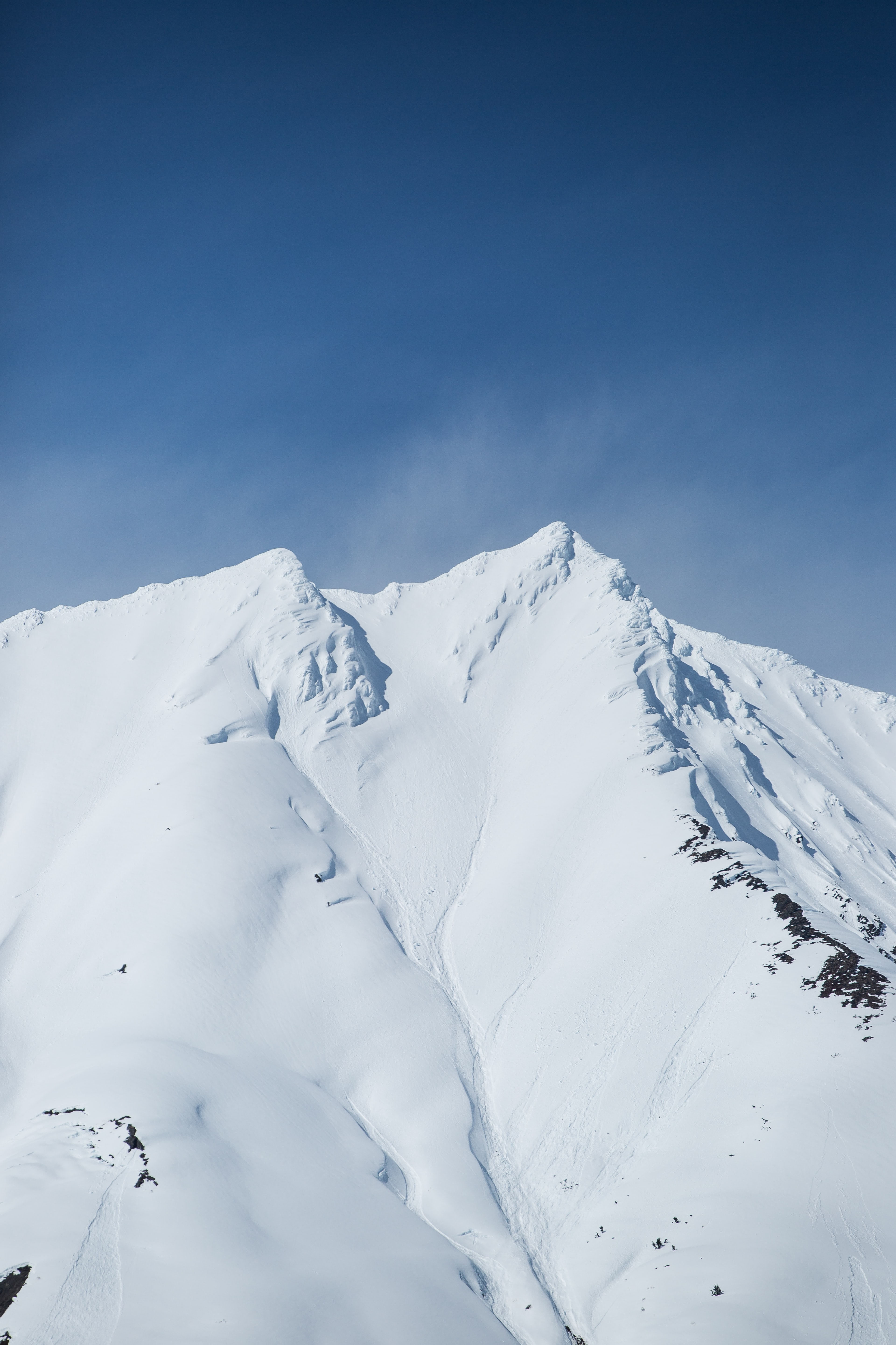 A mountain's crest covered in a thick layer of snow