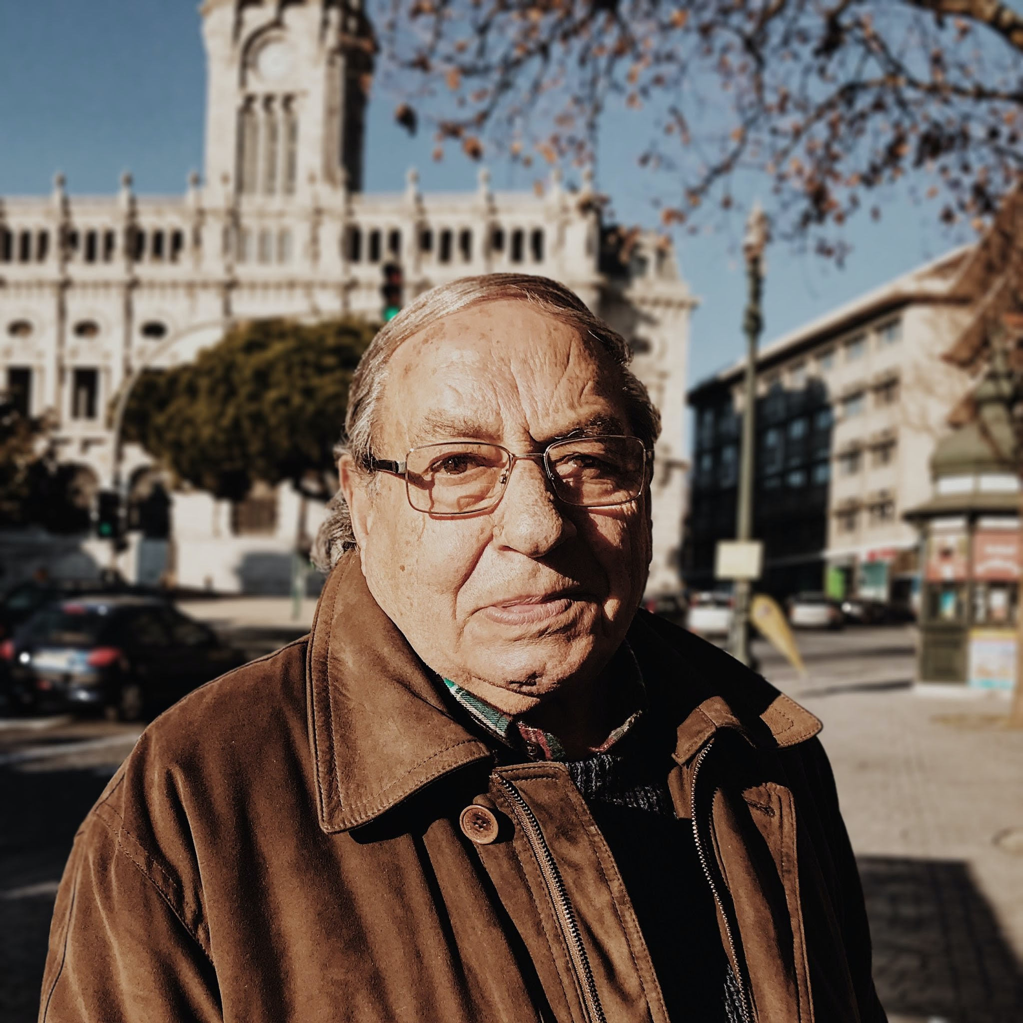 An elderly man with glasses staring blankly with the city behind him.