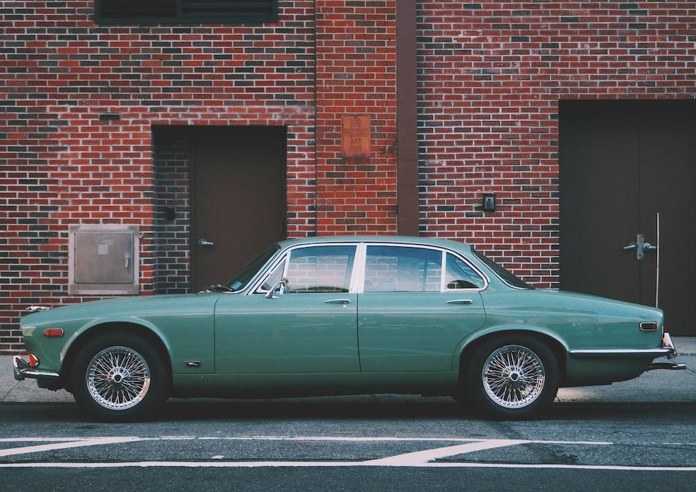 classic teal sedan near brown brick building at daytime