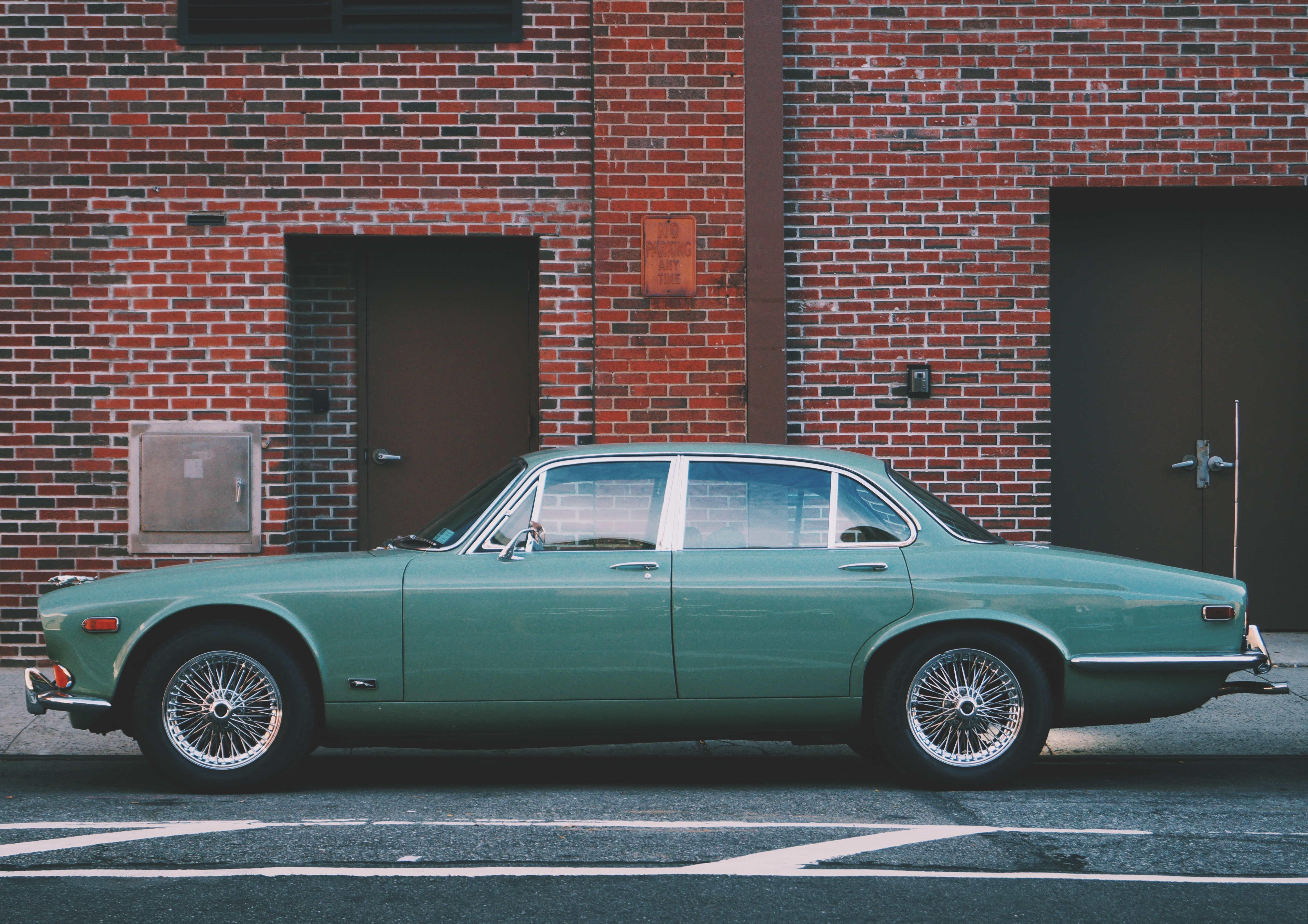 A classic green car is parked in front of a brick building in New York.